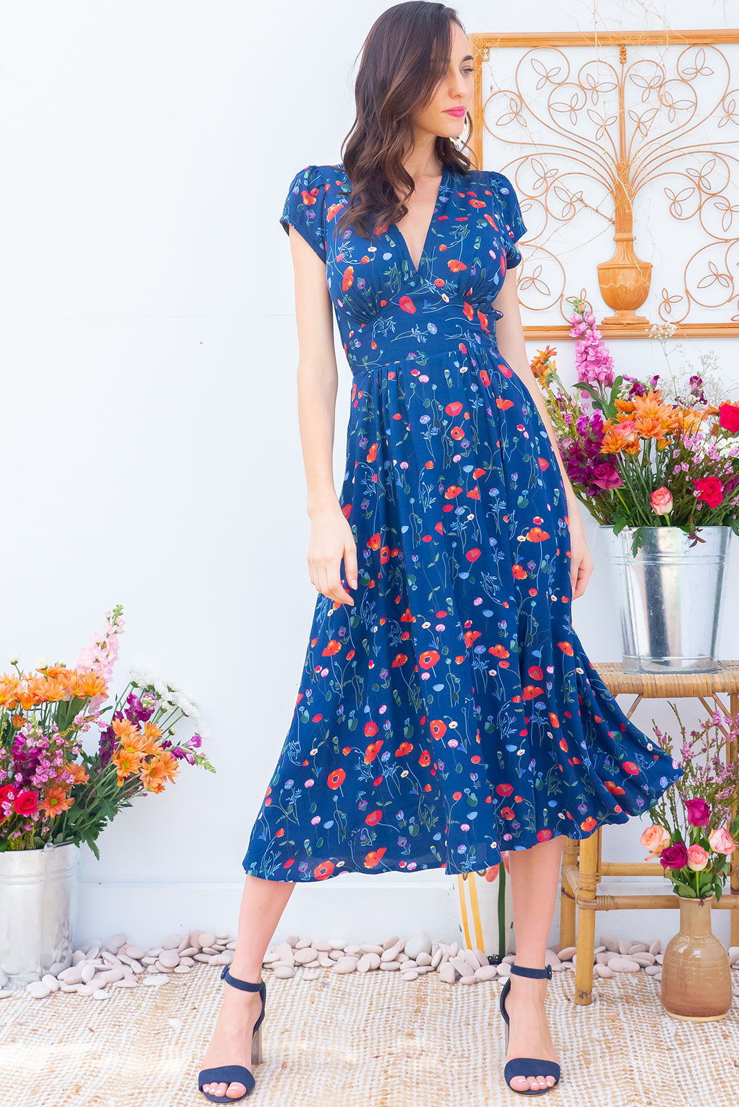Lizzie Lea Blue Midi dress features a vintage inspired fitted basque waist and elasticated waist with a cap sleeve and deep v neck the fabric is a soft woven rayon in a soft navy floral poppy print