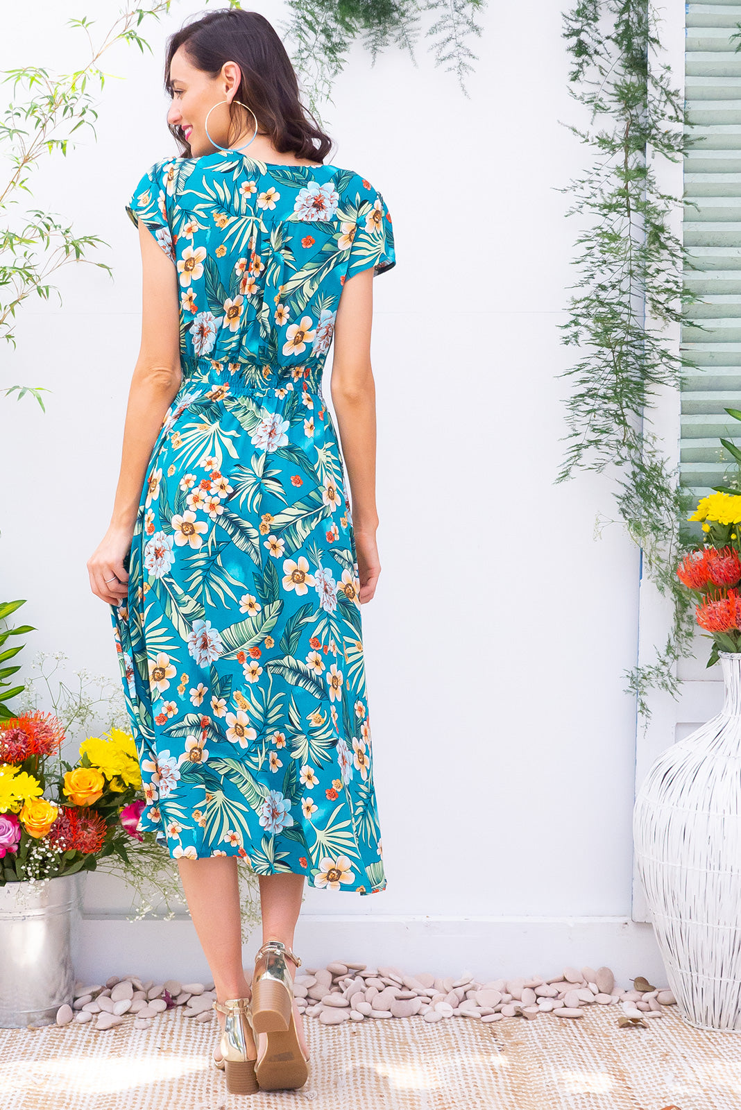 Lizzie Lucia Jungle Teal Midi dress features a vintage inspired fitted basque waist and elasticated waist with a cap sleeve and deep v neck the fabric is a soft woven rayon in a strong teal green tropical inspired floral print