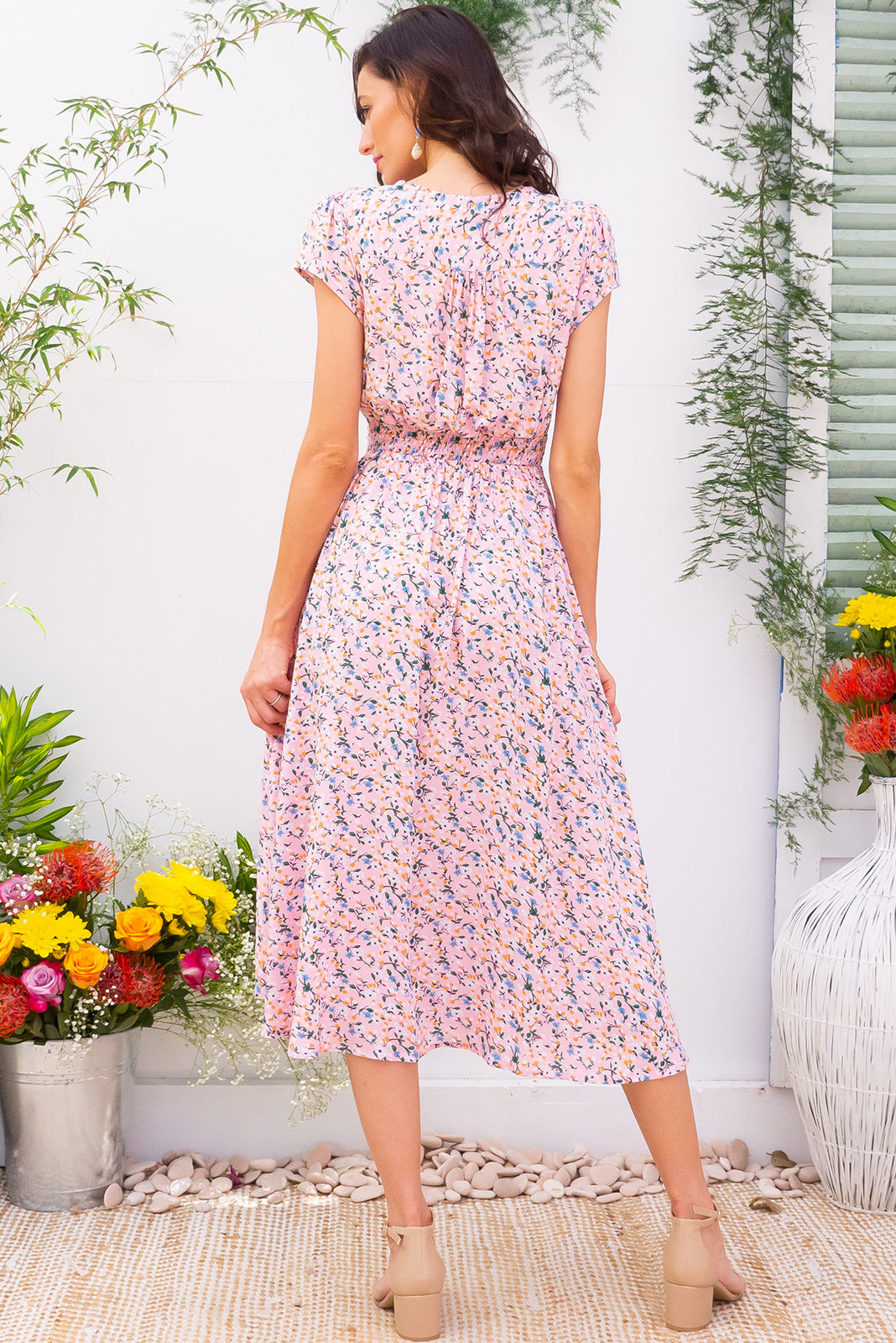 Lizzie Pink Lemonade Midi dress features a vintage inspired fitted basque waist and elasticated waist with a cap sleeve and deep v neck the fabric is a soft woven rayon in a soft petal pink floral print