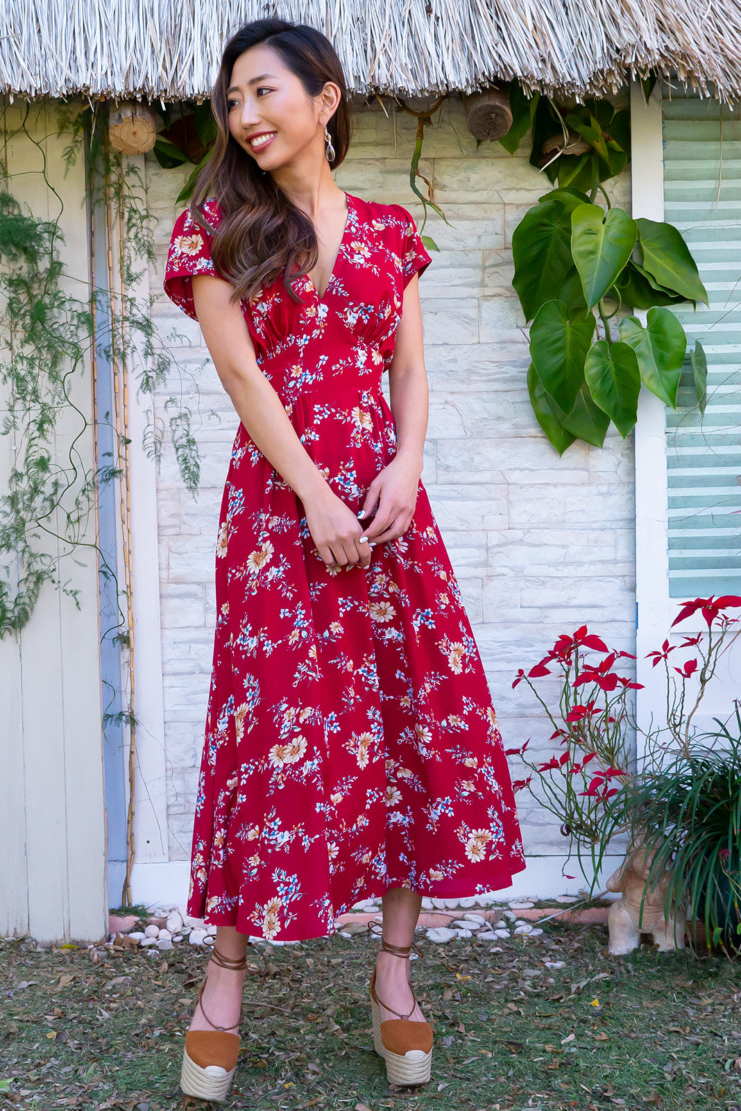 Lizzie Red Graces Midi dress features a vintage inspired fitted basque waist and elasticated waist with a cap sleeve and deep v neck the fabric is a soft woven rayon in a bright red floral print