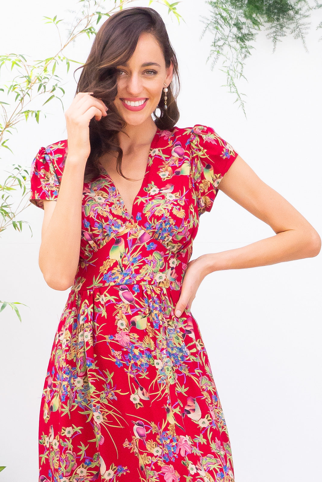 Lizzie Red Honey Eater Midi dress features a vintage inspired fitted basque waist and elasticated waist with a cap sleeve and deep v neck the fabric is a soft woven rayon in a bright red floral and bird print