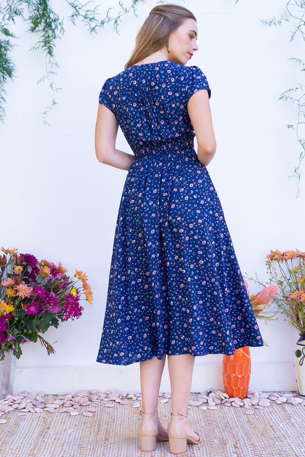 Lizzie Secret Blue Midi dress features a vintage inspired fitted basque waist and elasticated waist with a cap sleeve and deep v neck the fabric is a soft woven rayon in a soft navy floral watercolour print