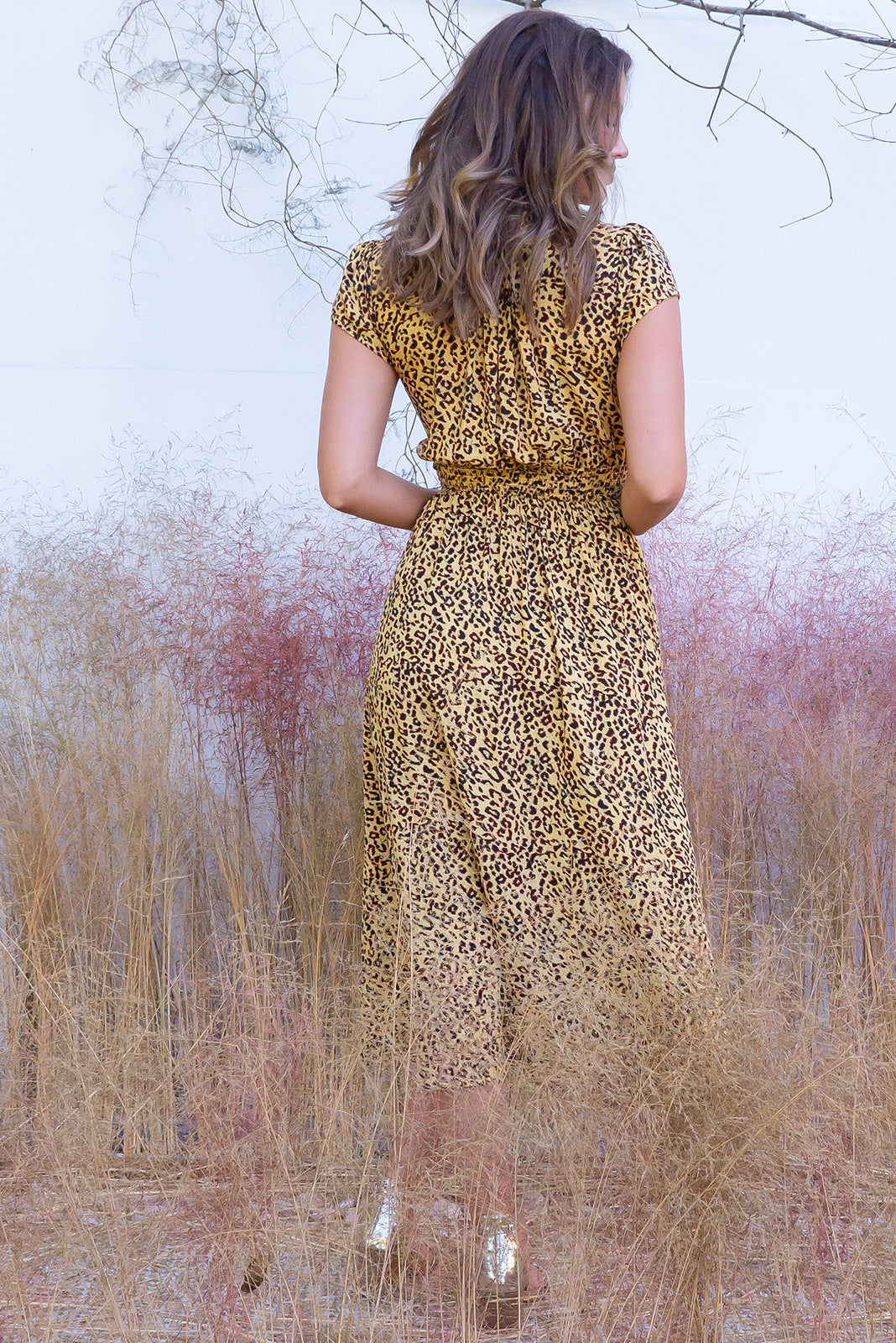 Lizzie Shona Golden Midi dress features a vintage inspired fitted basque waist and elasticated waist with a cap sleeve and deep v neck the fabric is a soft woven rayon in a soft yellow gold and brown tonal animal cheetah print