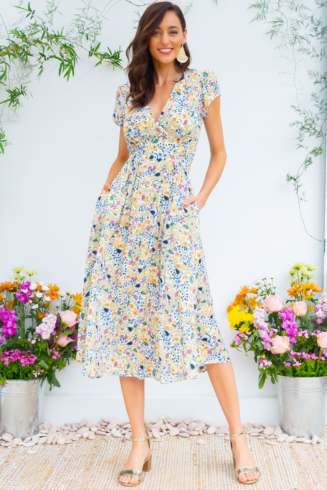 Lizzie Summer Garden Midi dress features a vintage inspired fitted basque waist and elasticated waist with a cap sleeve and deep v neck the fabric is a soft woven rayon in a soft warm white and intricate floral print
