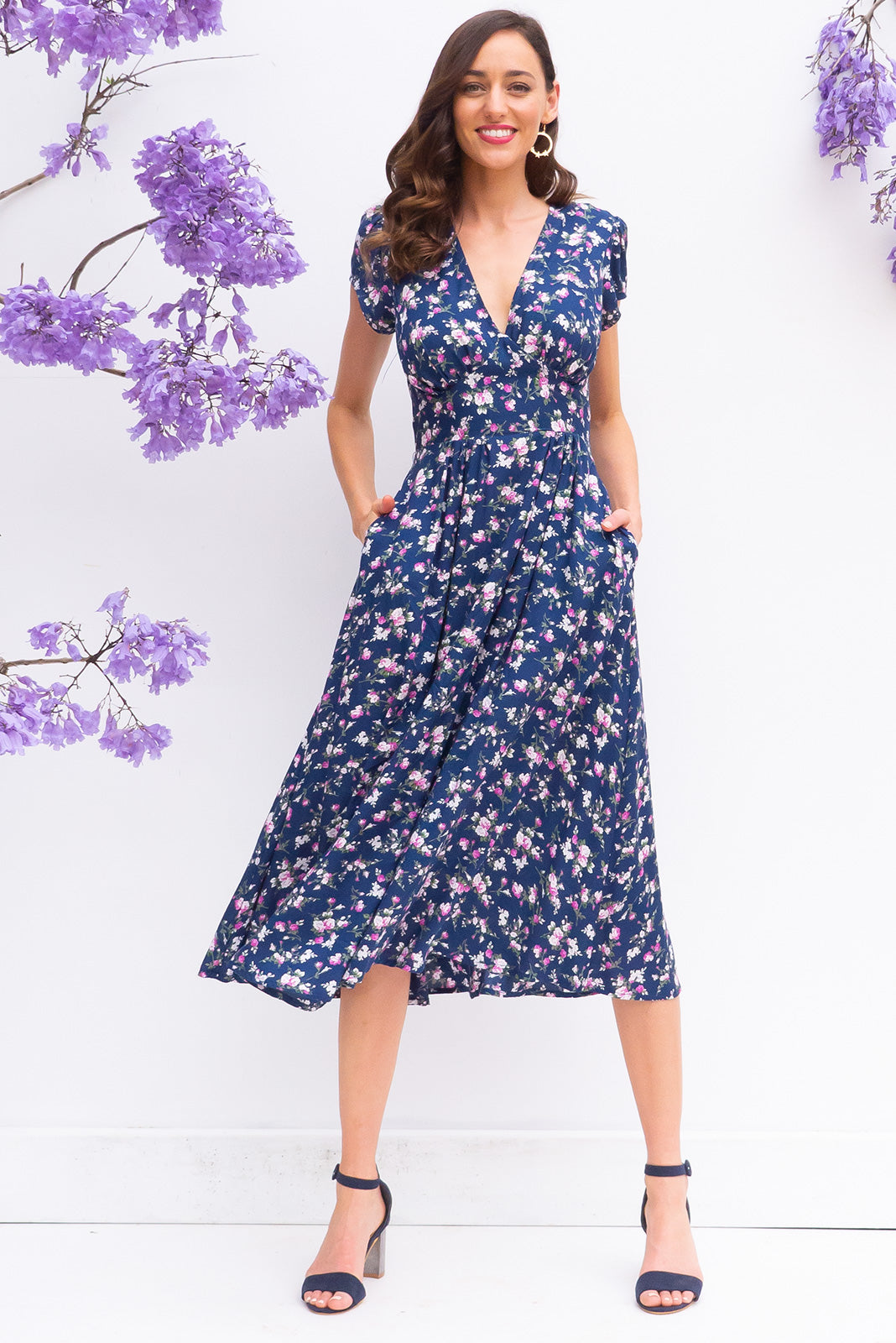 Lizzie Navy Tahalia Midi dress features a vintage inspired fitted basque waist and elasticated waist with a cap sleeve and deep v neck the fabric is a soft woven rayon in a bright navy small floral print