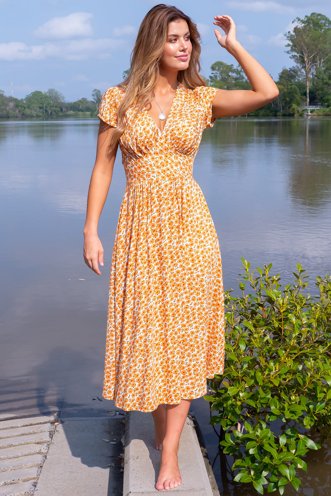 Lizzie Tangerine Dream Dress, vintage inspired frock is decorated in a soft white base with a fresh and fun orange daisy print of woven 100% rayon features lightweight/non-stretch fabric, waist features elastic shirring at back and side pockets.