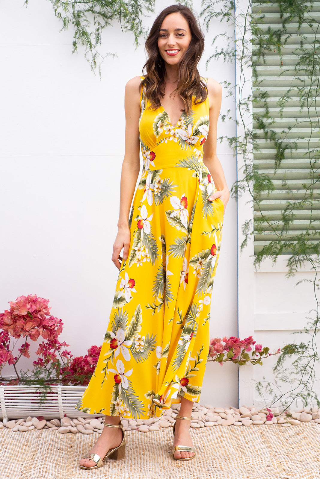 Lola Aloha Yellow Maxi dress features a fitted basque waist with an elasticated back with a slender strap and deep v neck the fabric is a soft woven rayon in a bright sunshine yellow tropical floral print