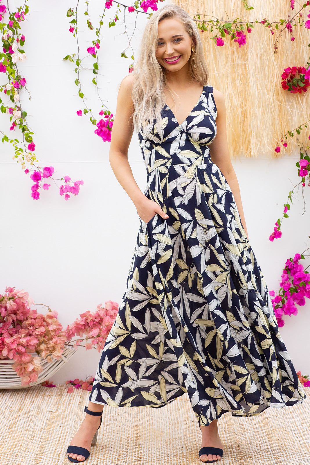Lola Chichi Navy Maxi Dress features a vintage inspired fitted basque waist and elasticated waist with a sleeveless design and deep v neck the fabric is a soft woven rayon in a navy, white and pale yellow leaf print