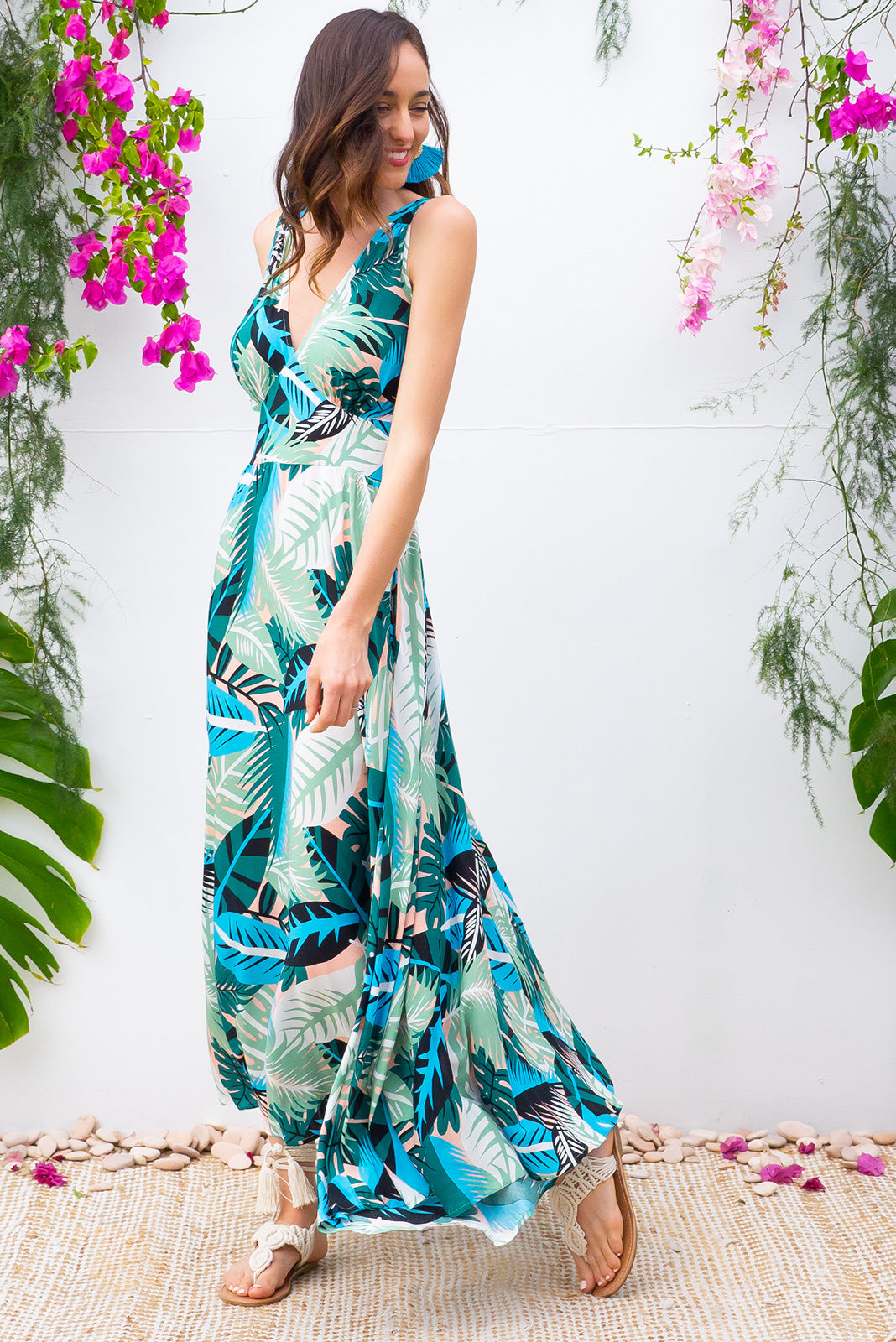 Lola Leafy Green Maxi Dress features a vintage inspired fitted basque waist and elasticated waist with a sleeveless design and deep v neck the fabric is a soft woven rayon in a navy, turquoise and pale green leaf print