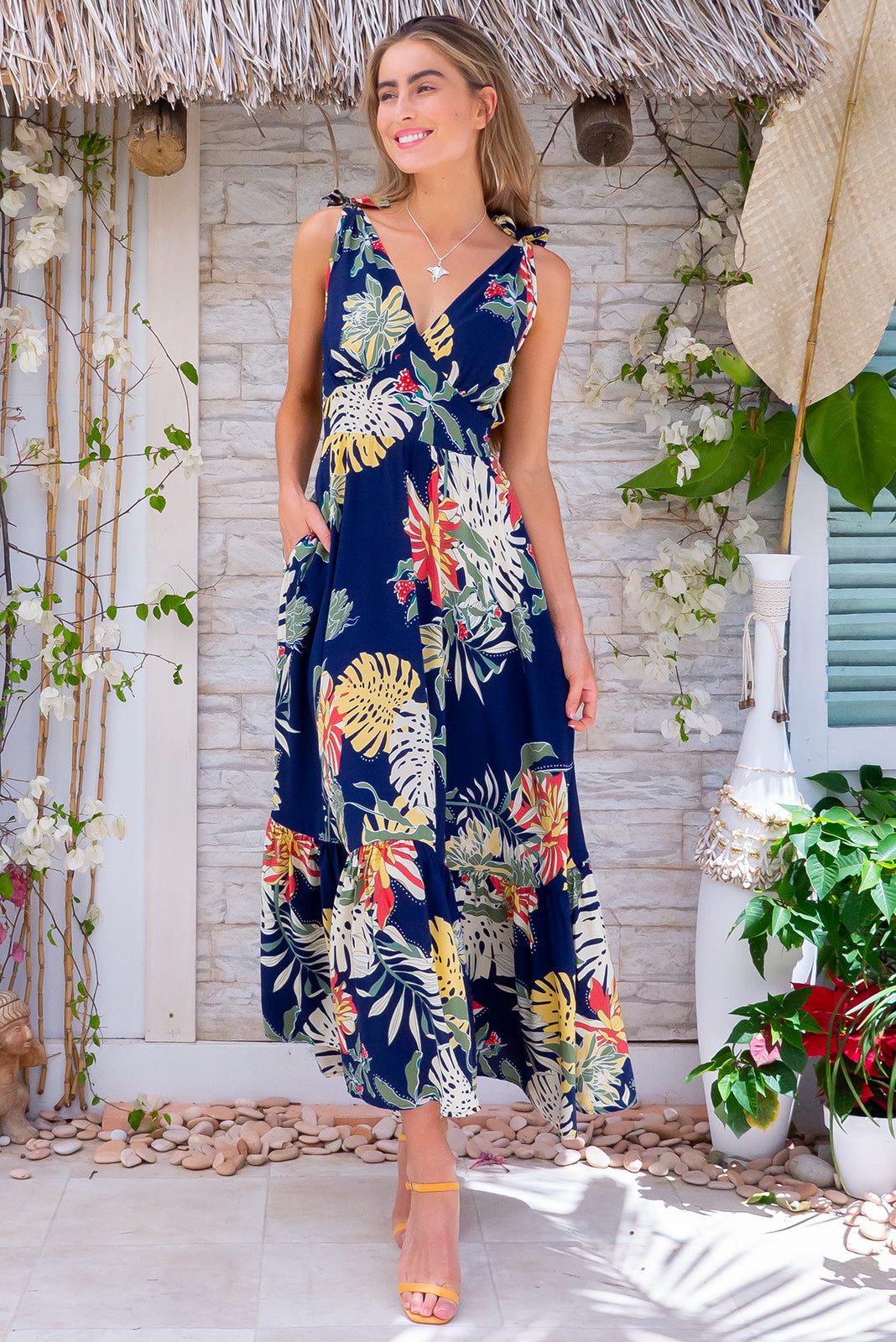 Luana Navy Palms Maxi Dress is made for twirling on the dance floor featuring adjustable tie up shoulders, shirred elasticated back waist, flattering front basque waist, side pockets in woven 100% viscose of deep navy base with multicoloured palm design featuring cream, coral, mustard and khaki.