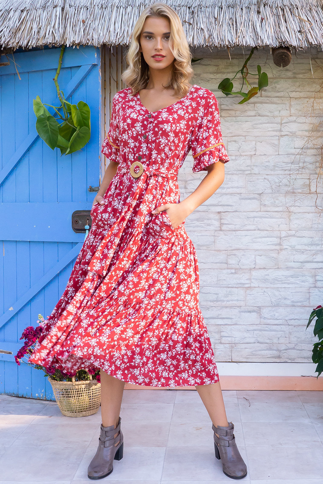 Lucinda Red Desert Maxi Dress features a frilled drop waist, button front, soft frill sleeves and a feature rattan buck belt the fabric is a soft crinkle textured woven 100% rayon in a rust red floral print