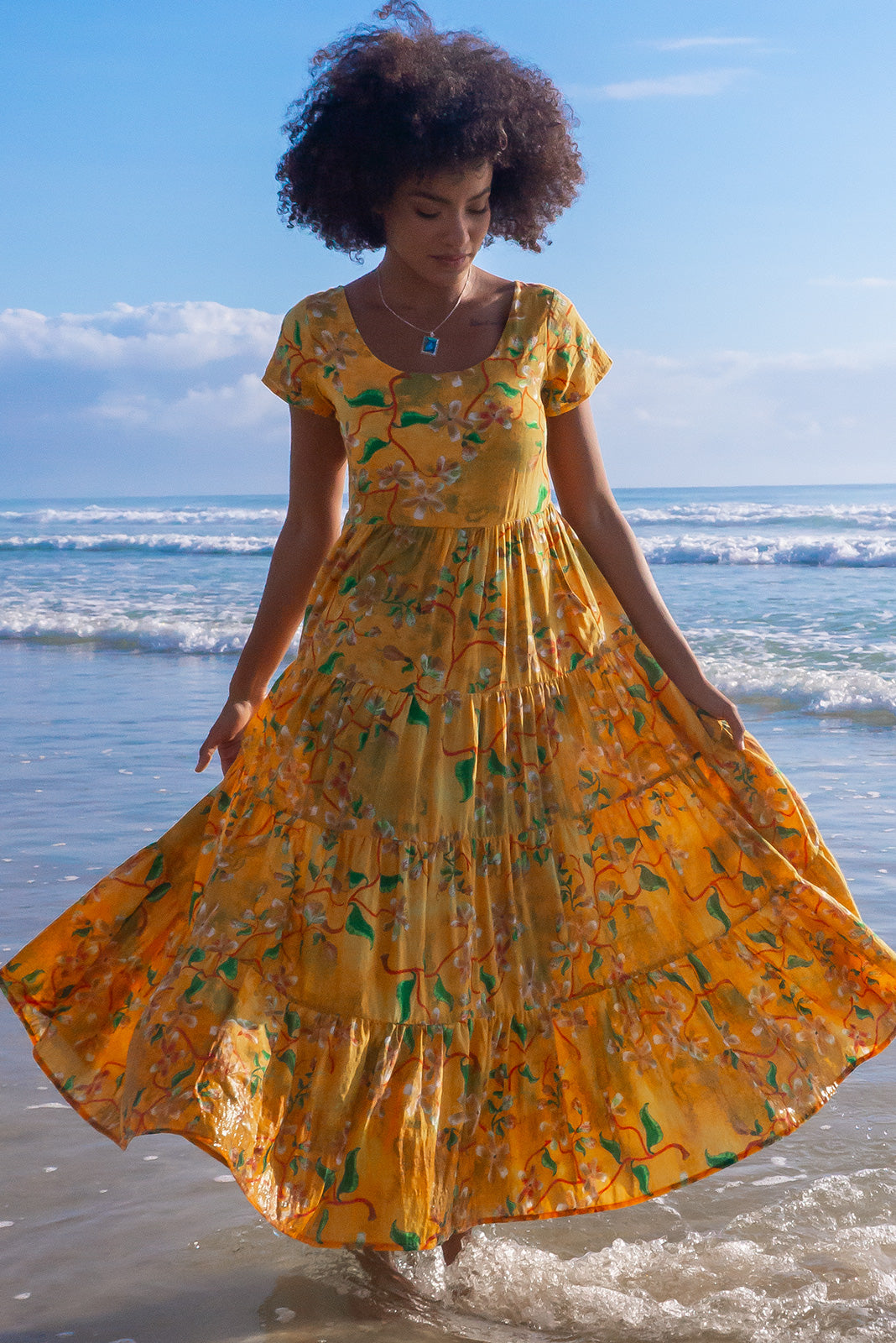 The Lucky Lulu Golden Garden Maxi Dress features scooped neckline, cap sleeves, side pockets, wide tiered skirt and 100% cotton in golden yellow and amber tone base with an abstract floral design and a light wash of moss green.