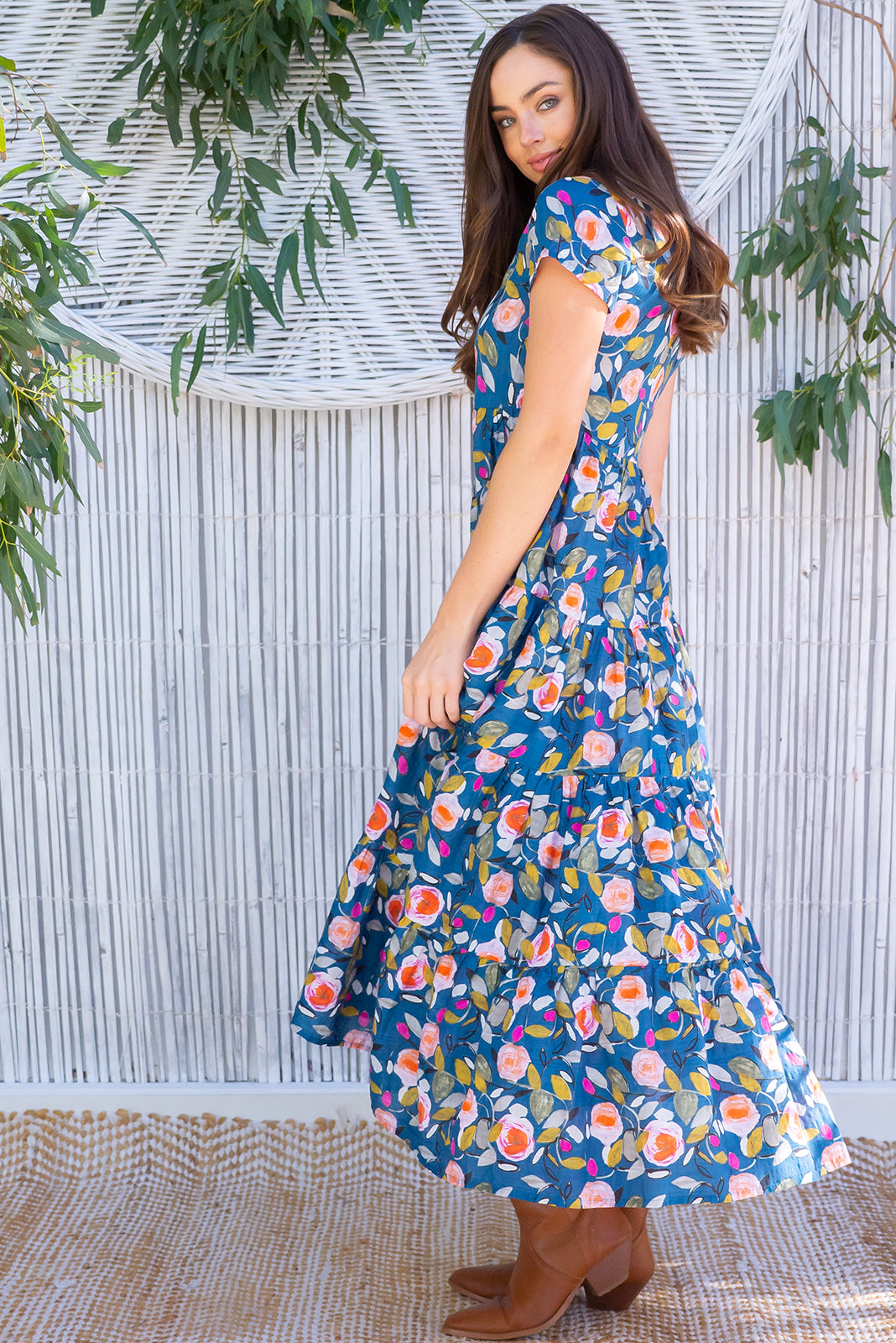 The Lucky Lulu Polka Rose Maxi Dress is inspired by vintage prints and beautiful gardens featuring scooped neckline, side pockets, navy/teal base with multicoloured rose design featuring fuchsia, peach, gold, mint and khaki in woven 100% cott