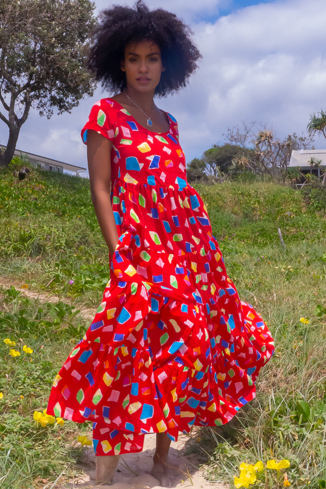 The Lucky Lulu Red Miro Maxi Dress features scooped neckline, cap sleeves, side pockets, wide tiered skirt and 100% cotton in bright red base with multicoloured shape design.