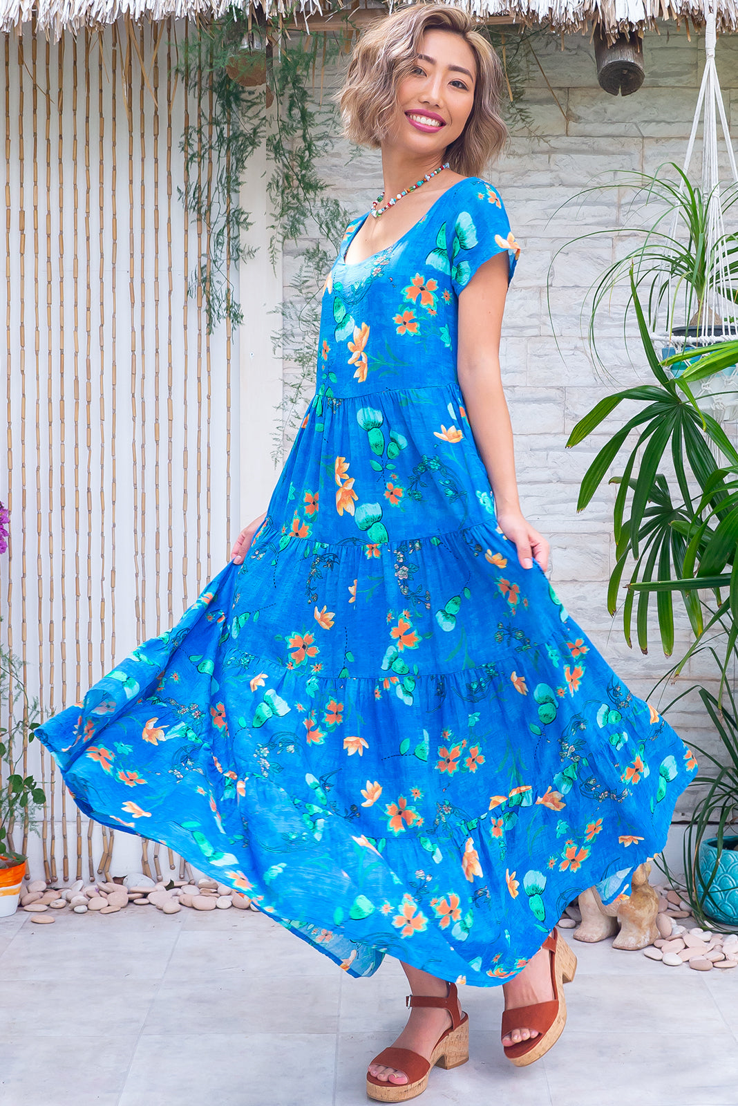 The Lucky Lulu Sapphire Maxi Dress features scooped neckline, cap sleeves, side pockets, wide tiered skirt and 100% cotton in azure blue wash effect base with orange and green floral motif.