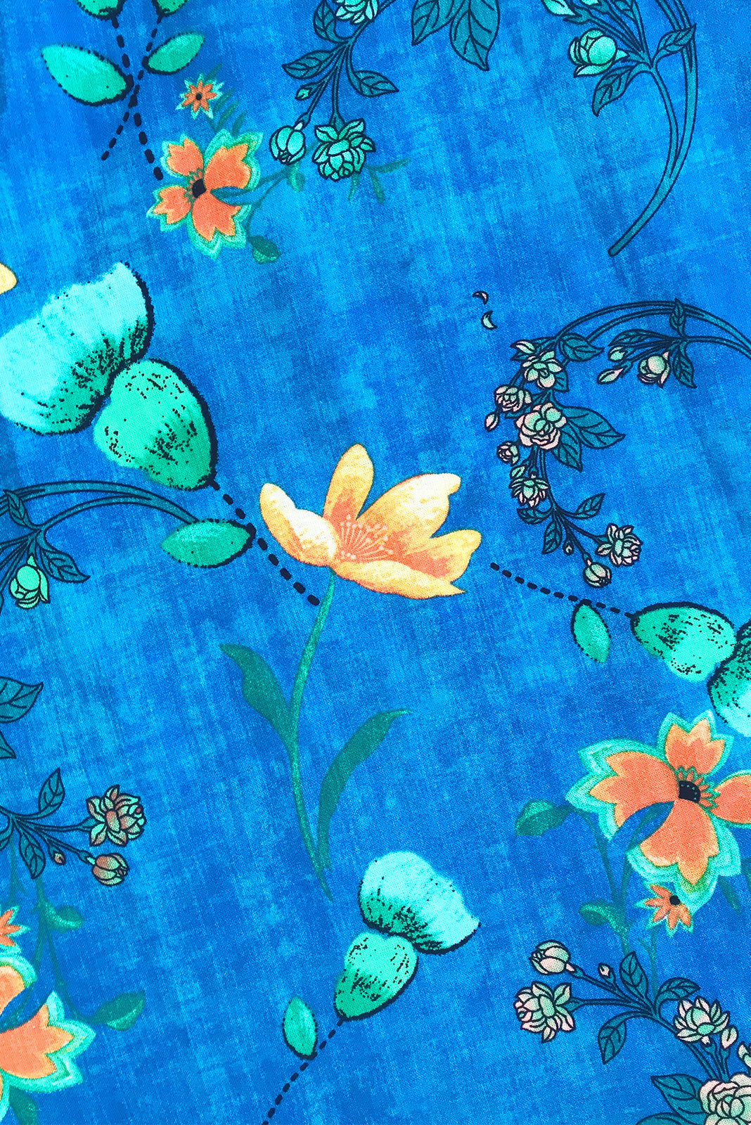 Fabric Swatch of  Lucky Lulu Sapphire Maxi Dress featuring 100% cotton in azure blue wash effect base with orange and green floral motif.