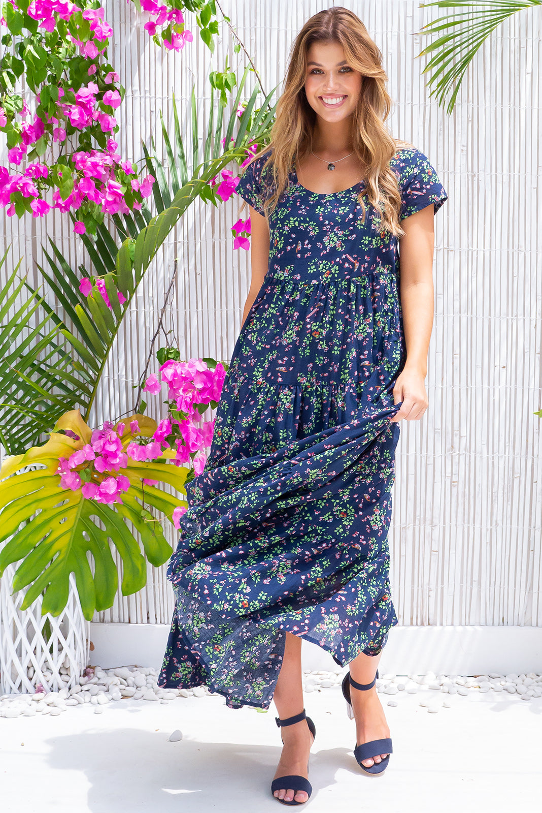 Lucky Lulu Navy Bayou Maxi Dress is a must-have navy dress featuring scooped neckline, cap sleeves, side pockets and a wide tiered skirt a deep navy base colour with floral print in woven 100% cotton.