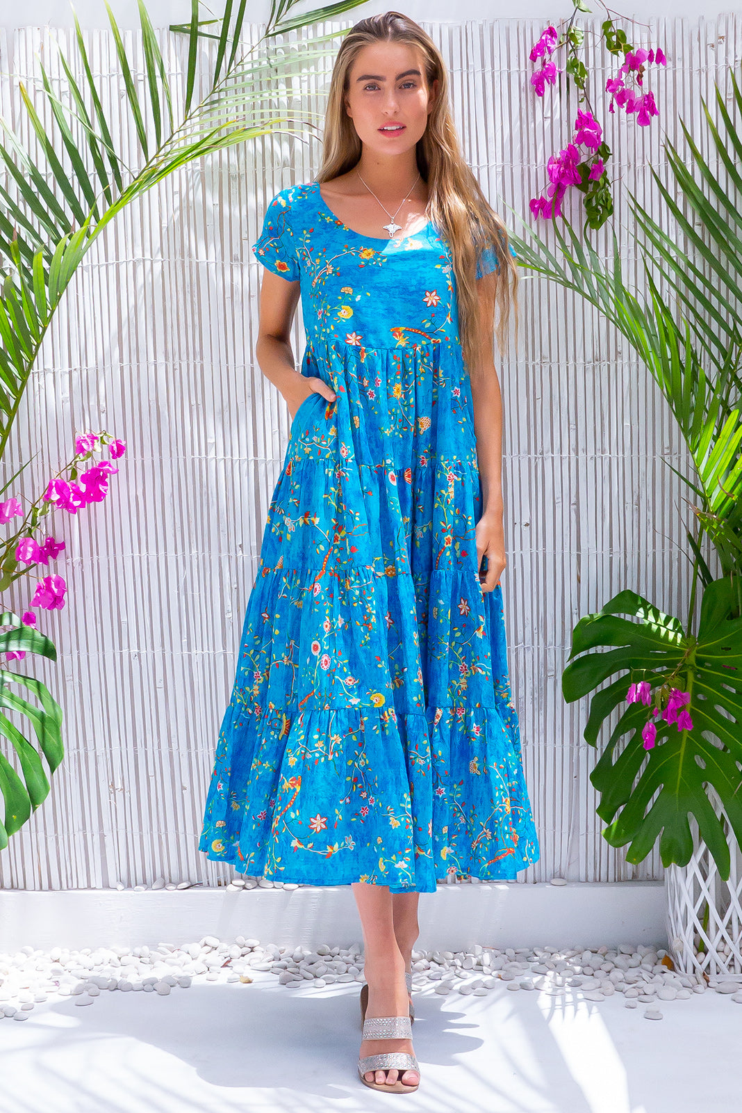 Lucky Lulu Pacific Blue Maxi Dress, bohemian summer style, 100% cotton, scooped neckline, capped sleeves, side pockets, wide four tiered skirt, bright blue base with medium multicoloured floral print featuring yellow, red, white and forest green.