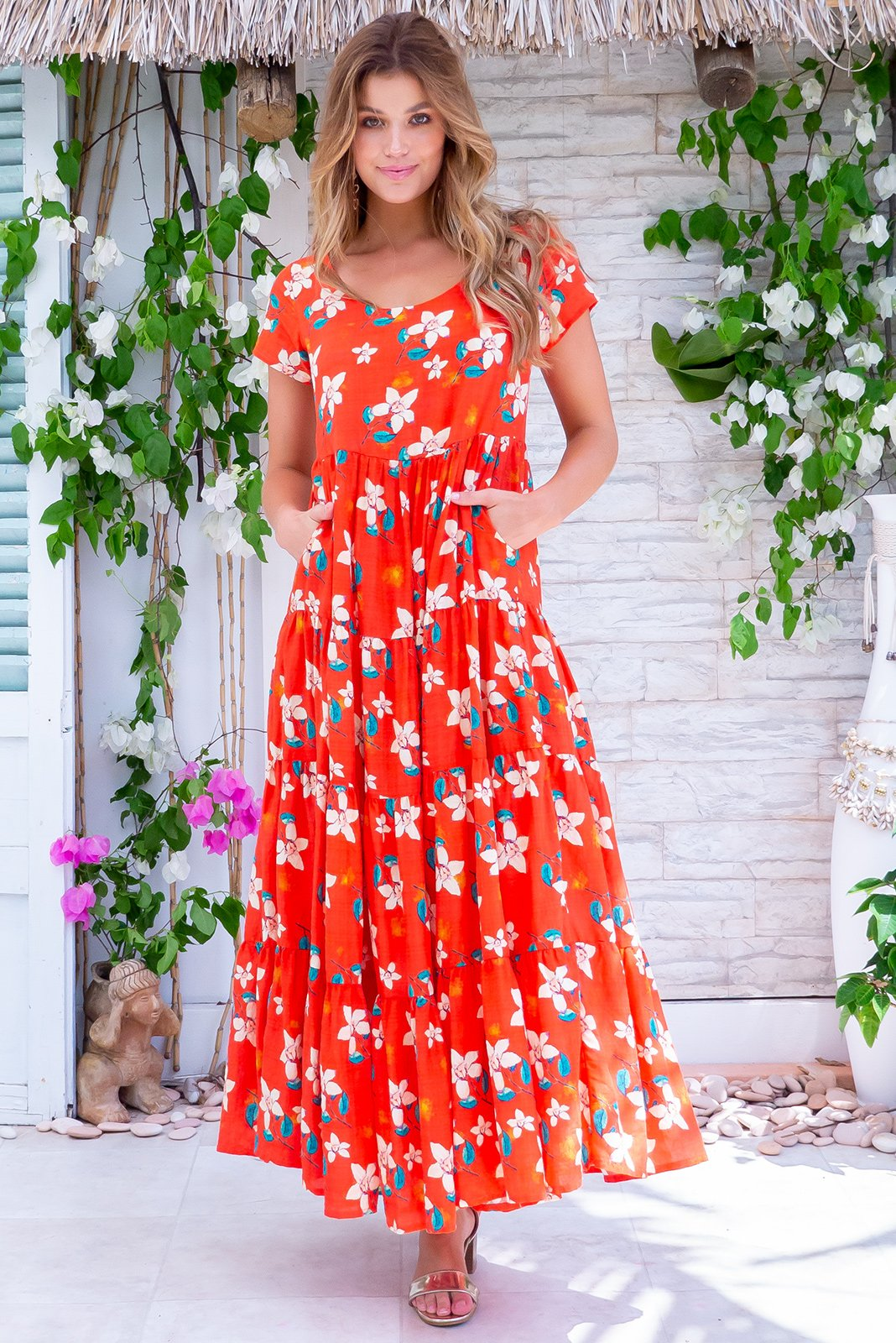 Lucky Lulu Really Red Maxi Dress is a must-have summer dress made in woven 100% cotton featuring  bright orange/red base with a fresh cream and green floral print, scooped neckline, cap sleeves, side pockets and wide tiered skirt.