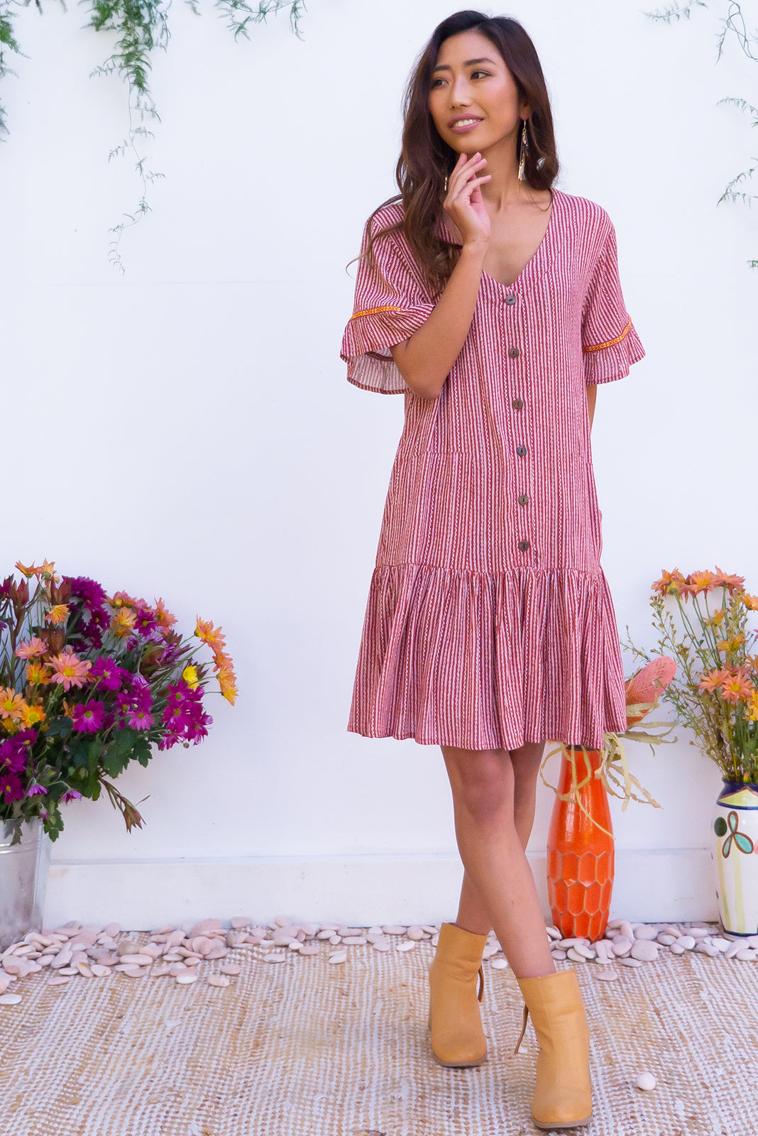 Lucy Ginger Beer Dress features a frilled drop waist, button front, soft frill sleeves and a feature rattan buck belt the fabric is a soft crinkle textured woven 100% rayon in a rust coloured stripe.