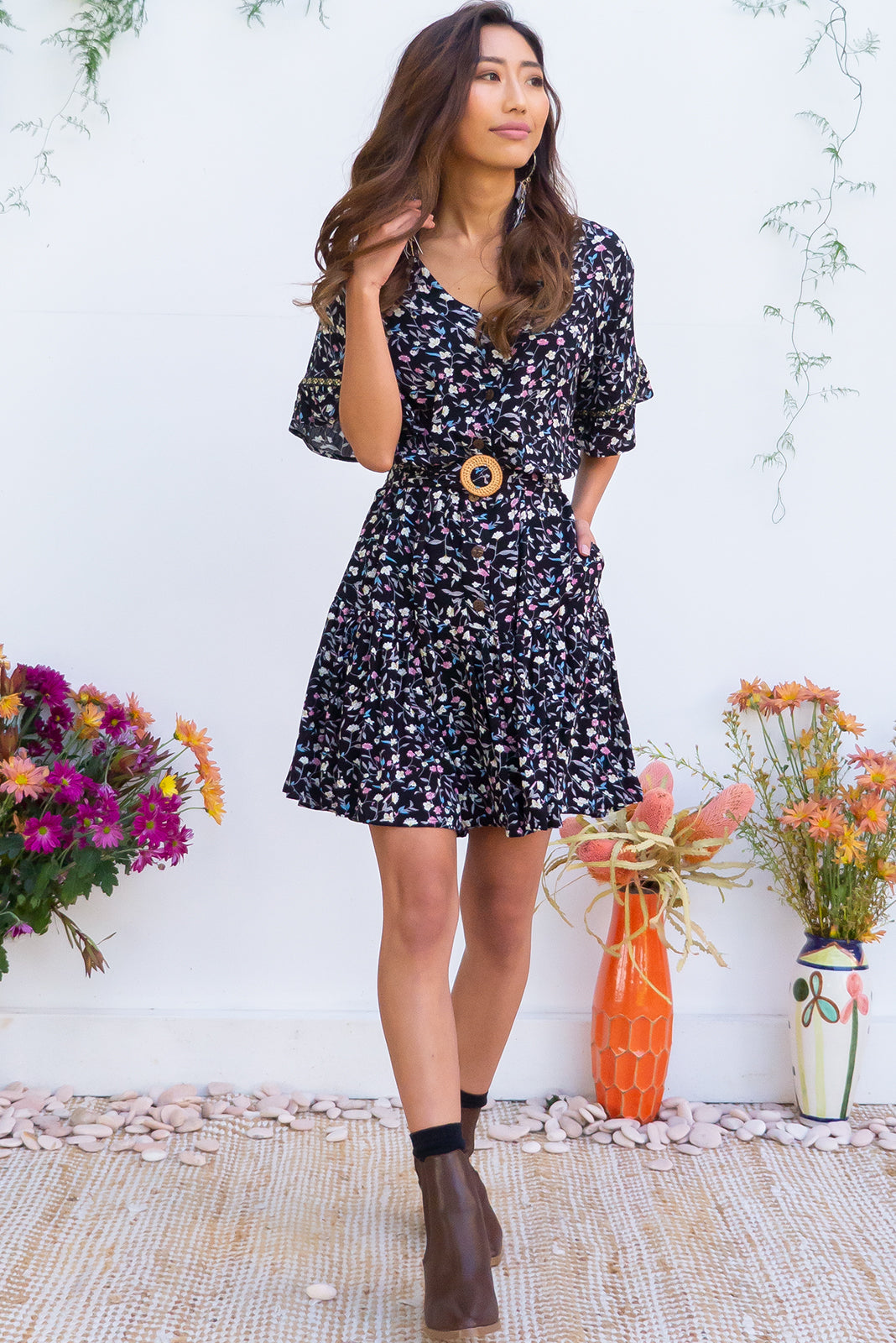Lucy Onyx Flowers Dress features a frilled drop waist, button front, soft frill sleeves and a feature rattan buck belt the fabric is a soft crinkle textured woven 100% rayon in a true black ditzy floral print