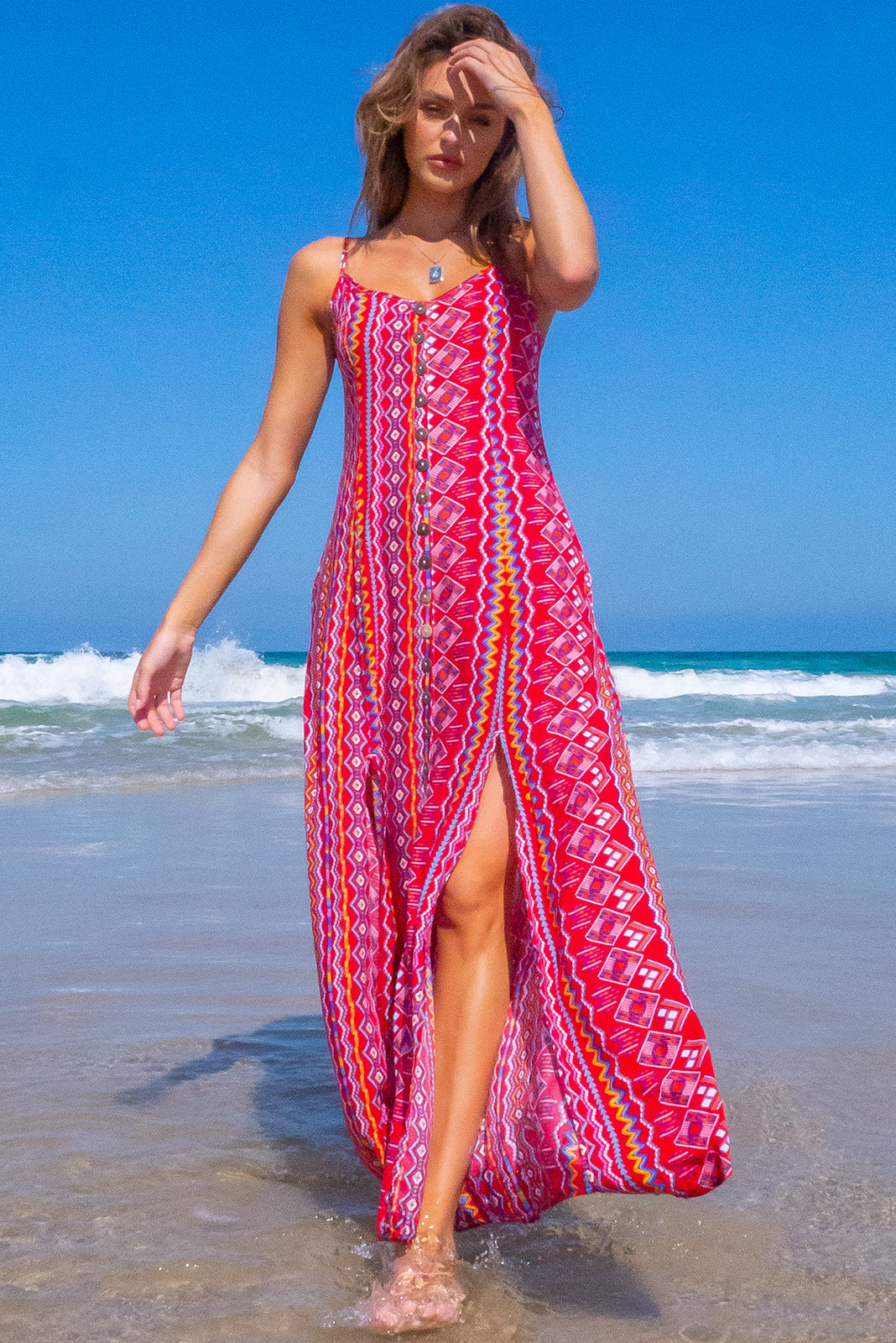 The Luella Mexicali Red Stripes Maxi Dress features coconut shell buttons down the front, scooped neckline, adjustable spaghetti straps, streamlined cut, front opening and two splits at the front sides of skirt, side pockets and 100%b viscose in red, retro aztec inspired stripe print.