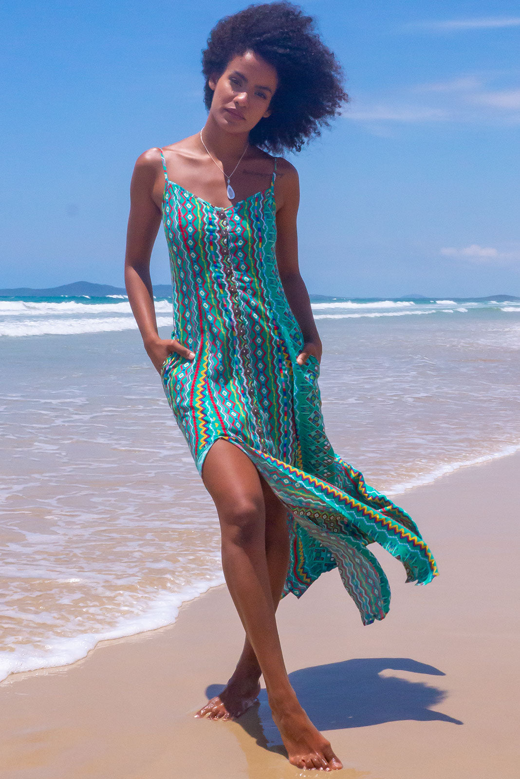 The Luella Paz Green Maxi Dress features coconut shell buttons down front, scooped neckline, adjustable spaghetti straps, streamlined cut, front opening and two splits at the front sides of skirt, side pockets and 100% rayon in green, retro aztec inspired stripe print.
