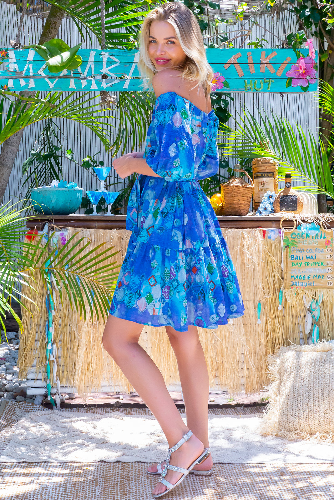 The Lulu Babe Blue Flair Swing Mini Dress is a 2-way cotton dress with blue, abstract mosaic print featuring off the shoulder style or on top of shoulders in scooped neck style and has small side pockets, fabric belt included to cinch in waist.
