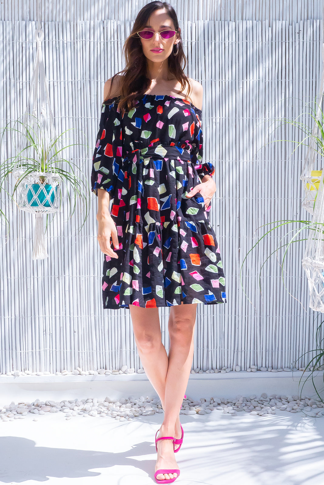 The Lulu Babe Calder Noir Swing Mini Dress now comes in fun print, featuring small side pocket, fabric belt included to cinch in waist, elasticated sleeve cuffs for puff effect and 100% cotton in black base with multicoloured shapes print.