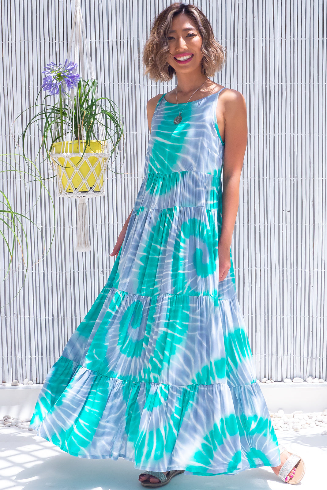 The Lulu Darling Aqua Ripples Maxi Dress features high neck with thin straps, tiered skirt falling from under bust, deep side pockets and 100% rayon in silvery grey and lagoon green ripple print.