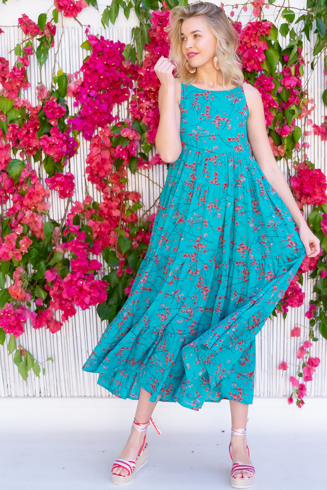 The Lulu Darling Bay Breeze Blue Maxi Dress features high neck with thin straps, full and tiered skirt, deep side pockets and 70% Cotton, 30% Rayon in bright teal base with orange oriental floral print.