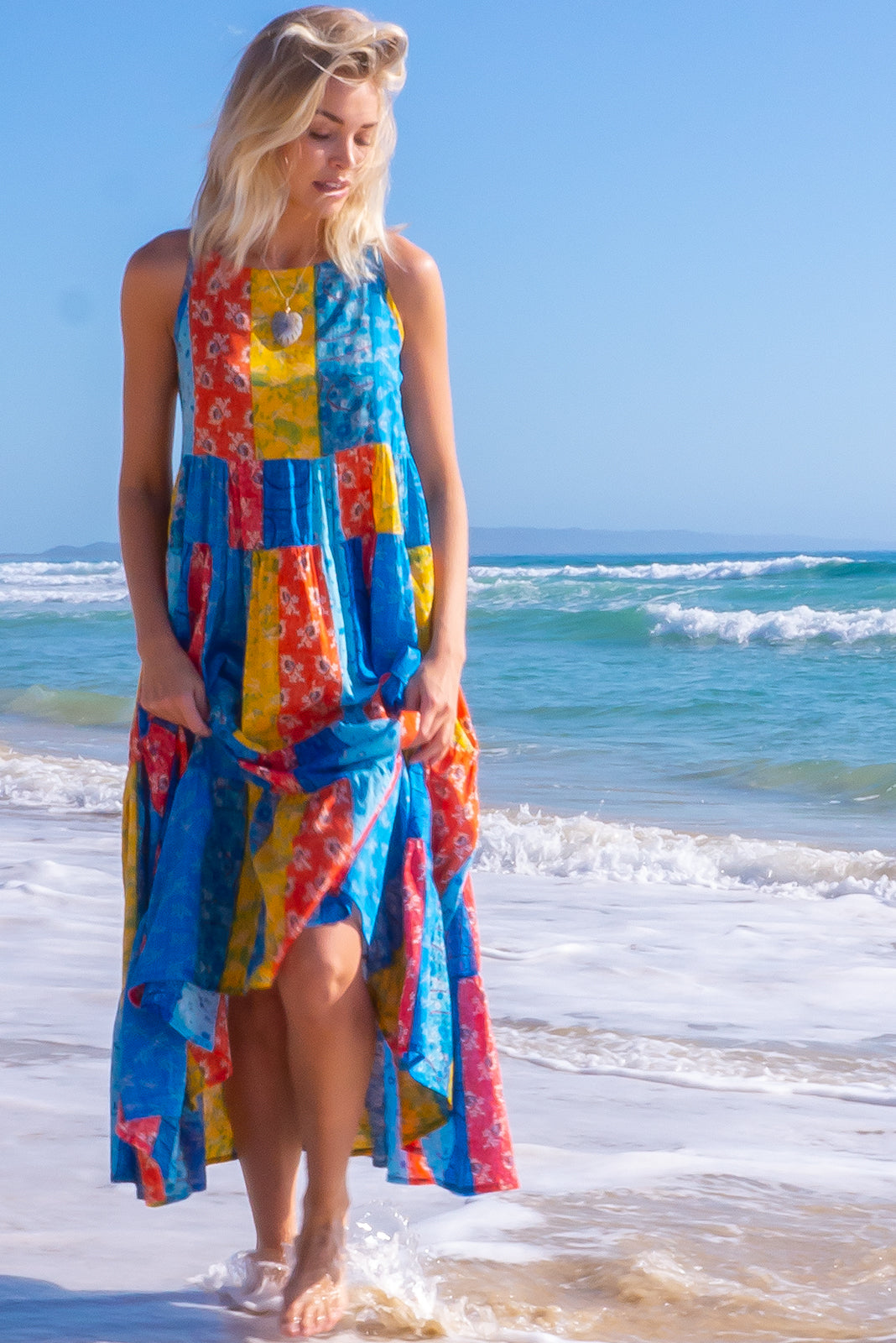 The Lulu Darling Cinque Stripes Maxi Dress features 66% Cotton, 34% Rayon, high neck with thin straps, full, tiered skirt falling from under bust, deep side pockets and blue, yellow, red and orange print.