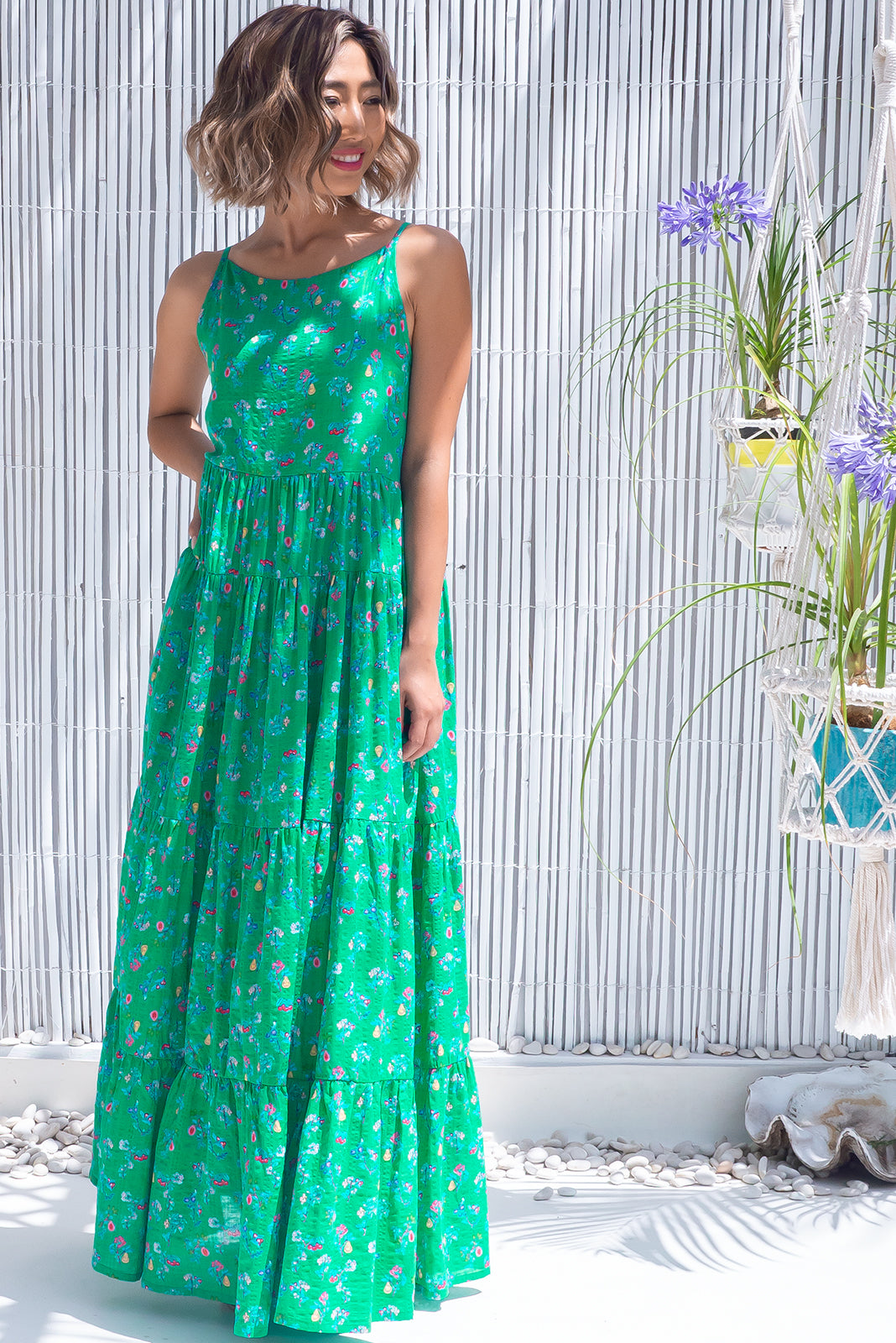 The Lulu Darling Green Fig Maxi Dress features high neck with thin straps, tiered skirt falling from under bust, deep side pockets and 100% cotton in vibrant green base with faint checker effect and blue/pink fruit print.