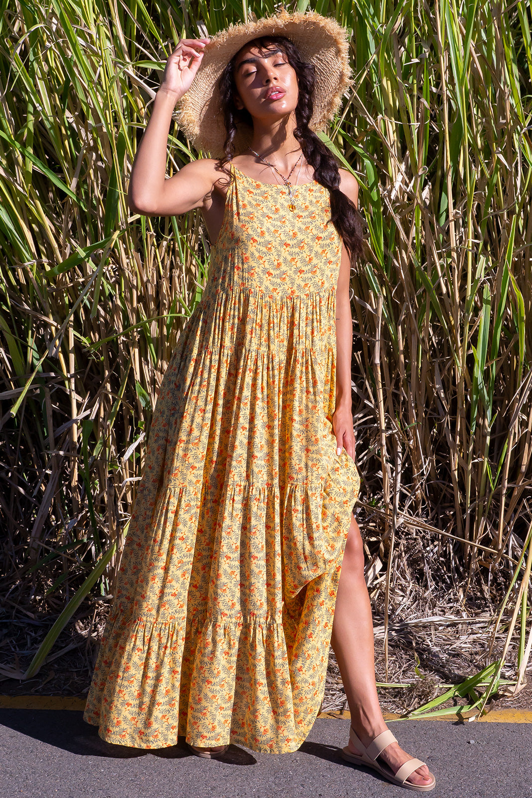 The Lulu Darling Honey Gold Maxi Dress features high neck with thin straps, full tiered skirt, deep side pockets and 70% Cotton, 30% Rayon in yellow base with orange and khaki print.
