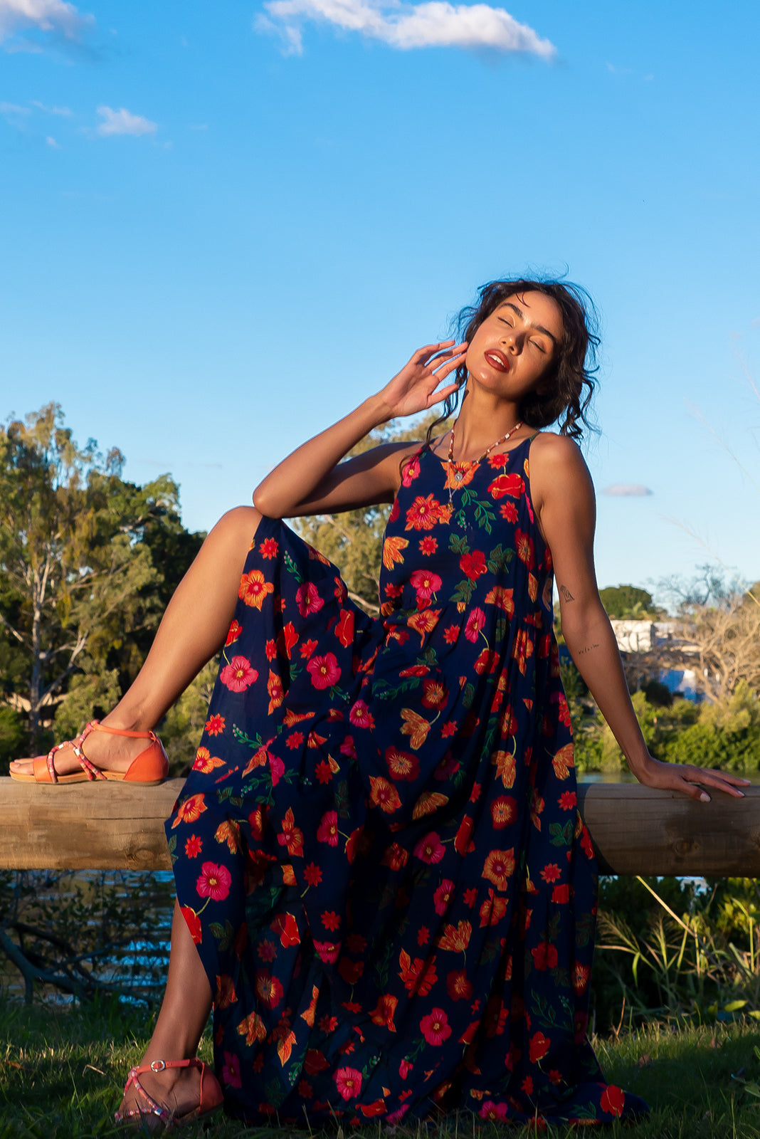 Lulu Darling Navy Kiss Maxi Dress features high neck with thin straps, full, tiered skirt falling from under bust, deep side pockets, 70% Cotton and 30% Rayon in bright deep navy base with colourful, bright floral print.