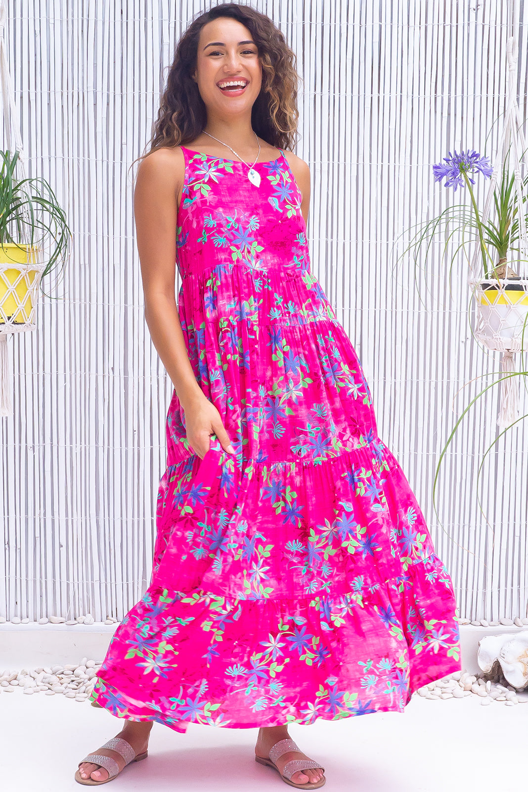 The Lulu Darling Panama Pink Maxi Dress features high neck with thin straps, tiered skirt falling from under bust, deep side pockets and 100% rayon in vibrant pink base with wash effect and blue/green florals.