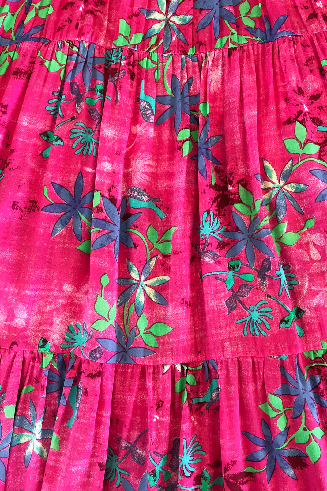 Fabric swatch o fLulu Darling Panama Pink Maxi Dress featuring 100% rayon in vibrant pink base with wash effect and blue/green florals.