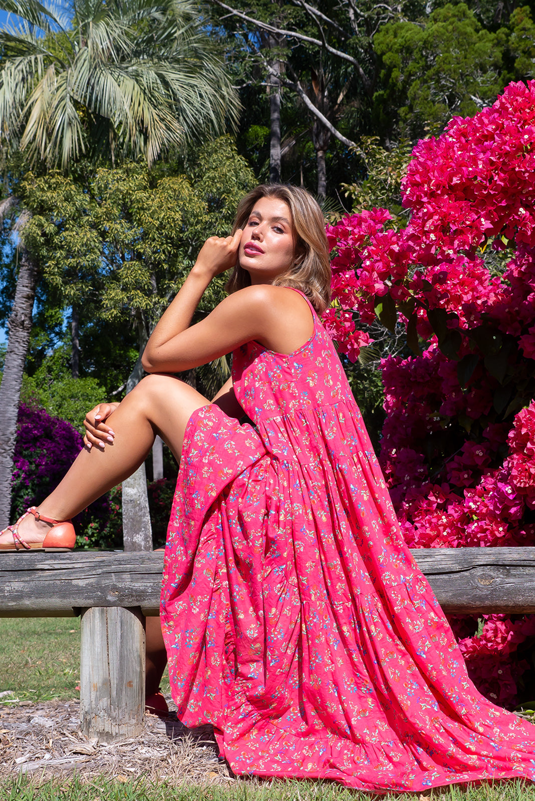 The Lulu Darling Watermelon Fig Maxi Dress features high neck with thin straps, full, tiered skirt falling from under bust, deep side pockets and 70% Cotton, 30% Rayon IN Watermelon base with small fruit print.