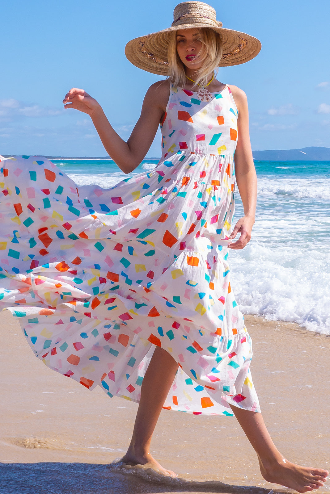 The Lulu Darling White Miro Maxi Dress features high neck with thin straps, full, tiered skirt falling from under bust, deep side pockets and cotton/rayon blend. in white base with scattered colourful shapes.