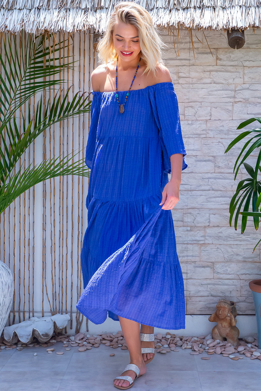 The Lulu Liberty Blue Dobby Swing Maxi Dress can be worn 2 ways, off the shoulder style or on top of shoulders in scooped neck style, this beauty features fabric belt included and 100% textured cotton in blue with spot texture and faint plaid print.