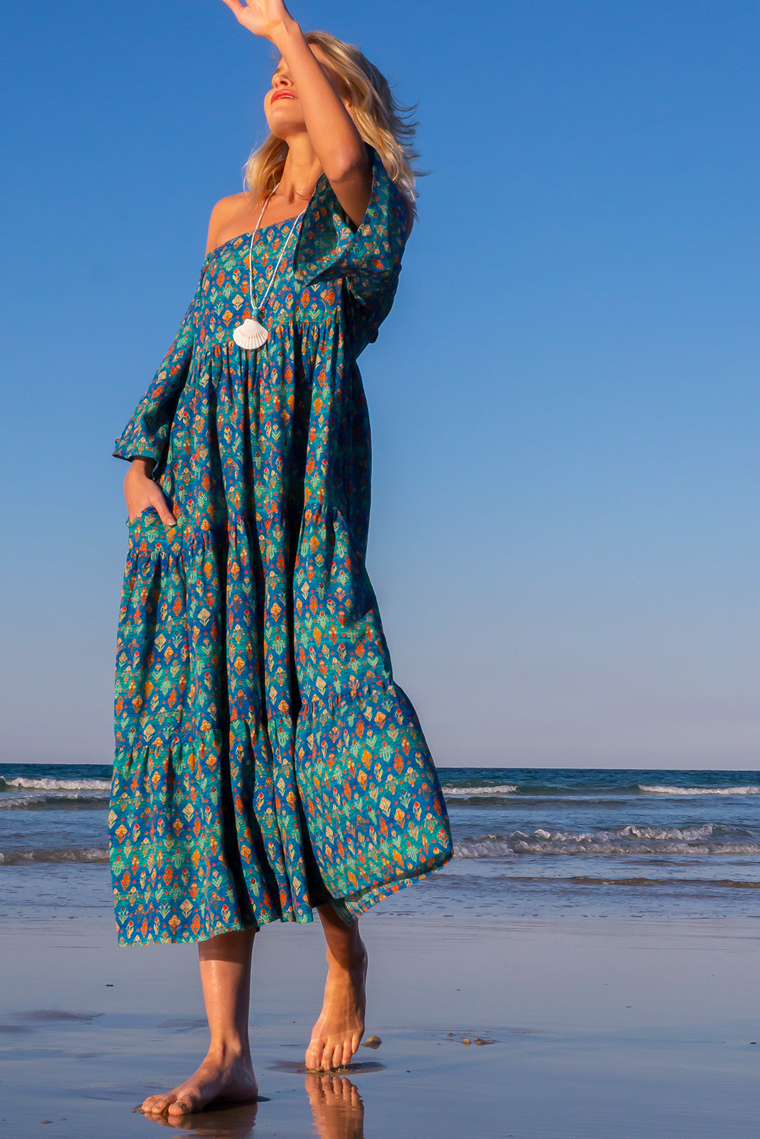 The Lulu Liberty Turquoise Aztec Swing Maxi Dress can be worn 2 ways, off the shoulder or on top of shoulders in scooped neck style and features keyhole style back detail with adjustable tie, fbric belt and 100% cotton in turquoise tie dye effect base with aztec print.