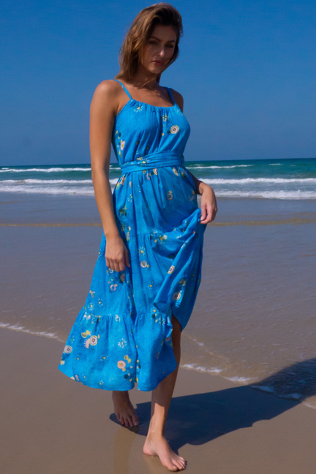 The Lulu Loves Clear Water Blue Maxi Dress featuring a tiered skirt, hidden side pockets and 100% cotton in blue wash effect base with abstract floral print.