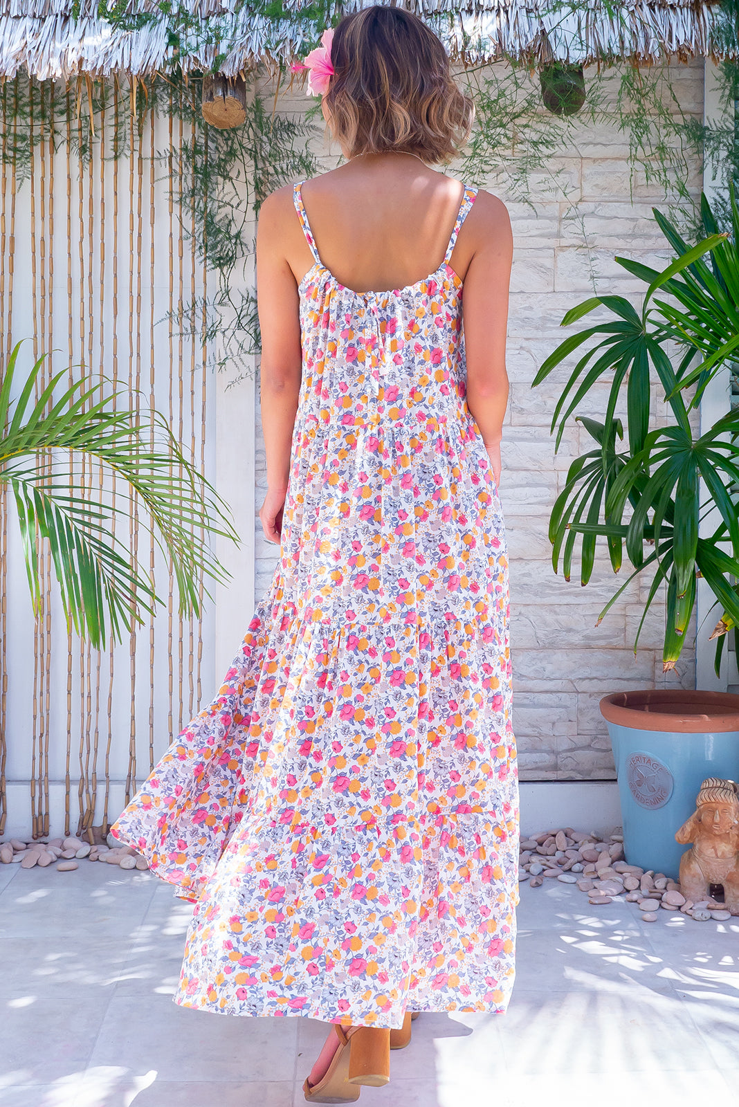 The Lulu Loves Fields of Dreams Maxi Dress features sleeveless design with adjustable neck tie, hidden side pockets, including self-coloured belt and 100% cotton in off white base with amber and pink flowers & silver vines.