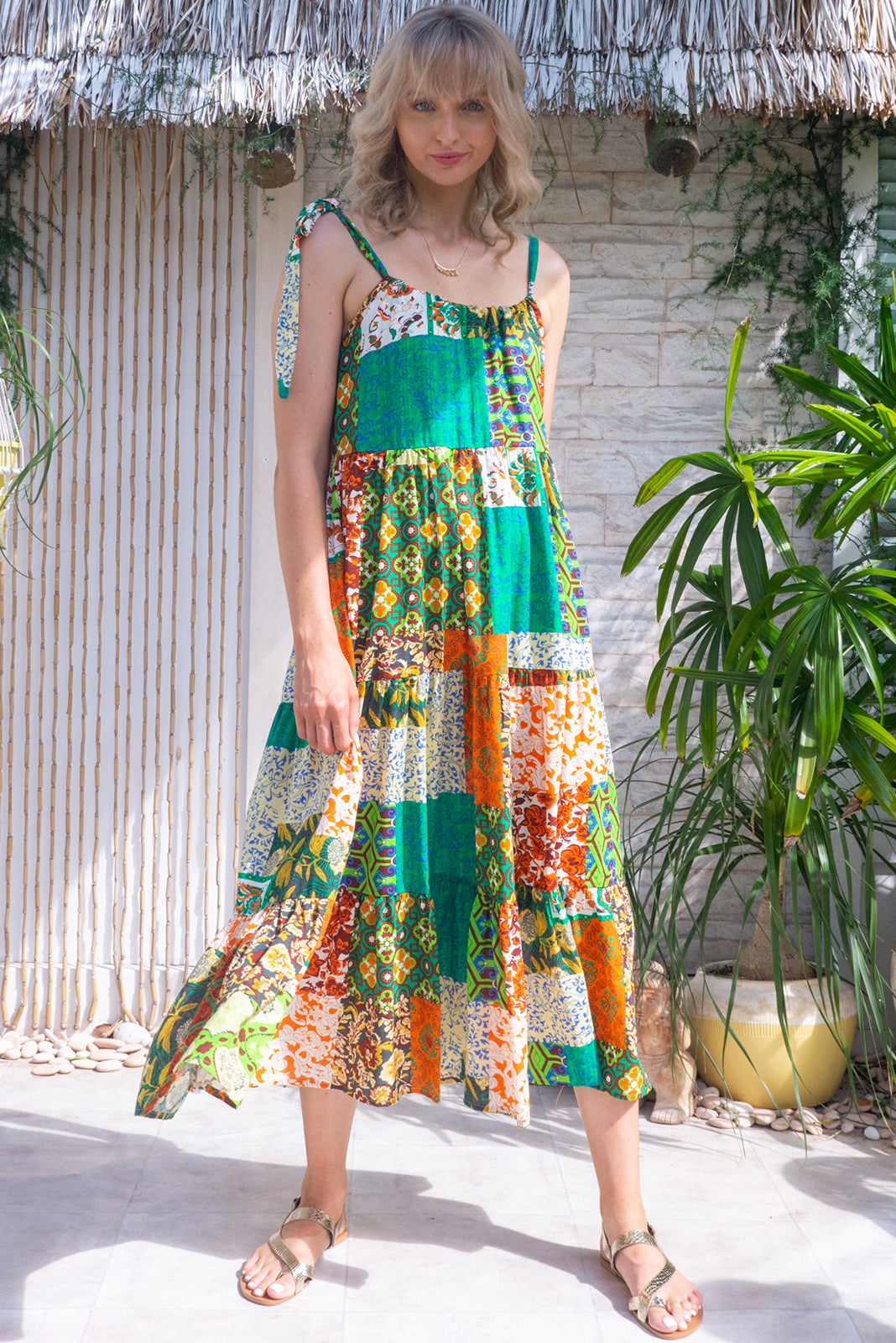 The Lulu Loves Green Mosaic Maxi Dress features tiered skirt, sleeveless design with adjustable neck tie, hidden side pockets, 100% cotton in green, orange and yellow patchwork print and includes self-coloured belt.