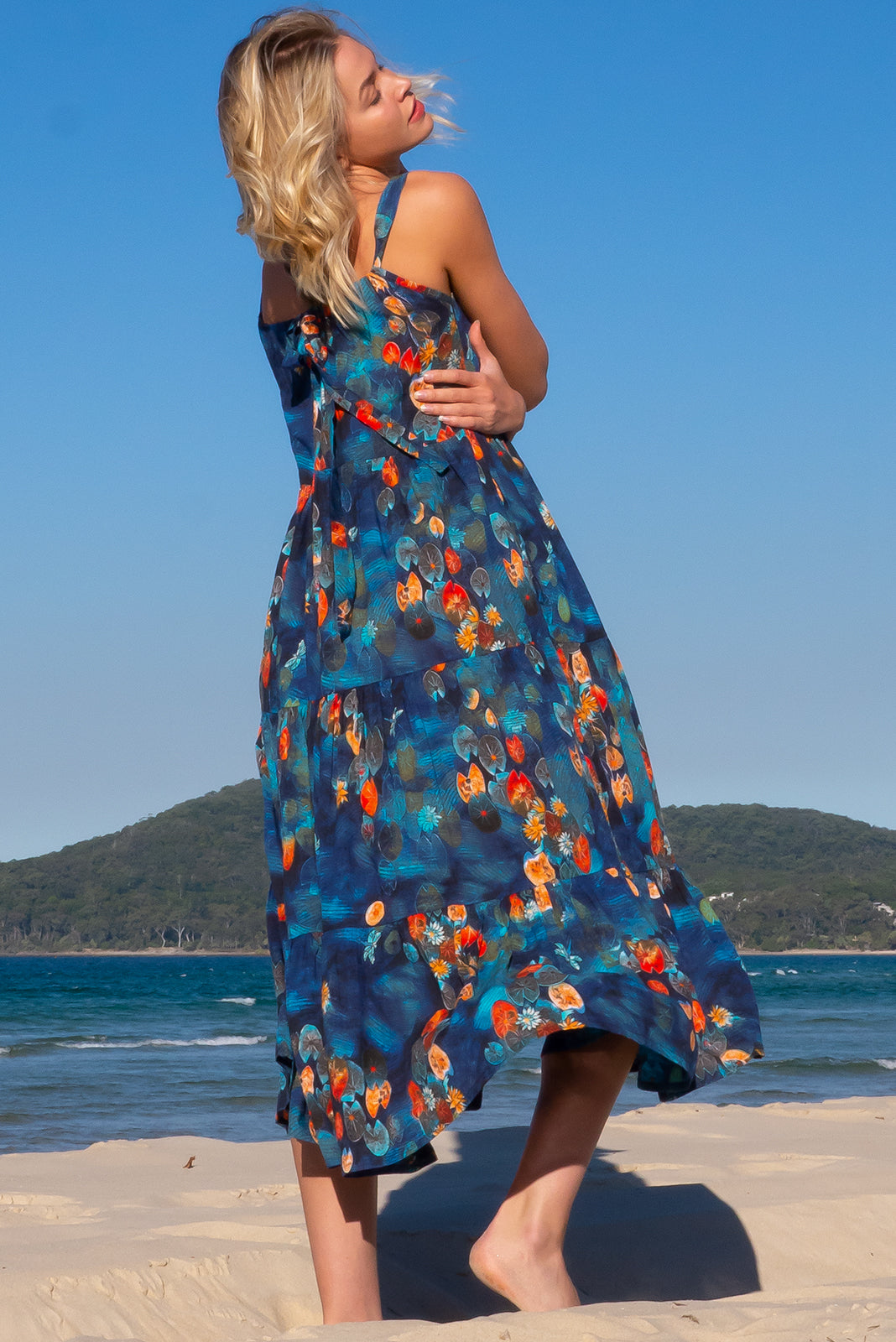 The Lulu Loves Lilly Pond Maxi Dress is a oversized maxi dress featuring a tiered skirt, sleeveless design with adjustable neck tie, hidden side pockets and 100% cotton in navy base with lilly pond print.