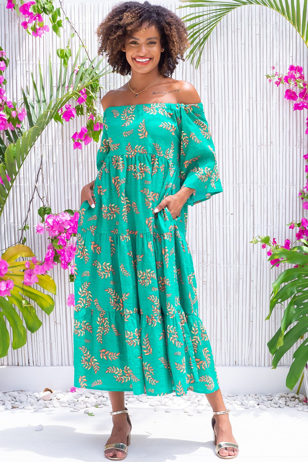 The Lulu Liberty Green Shadow Leaf Maxi Swing Dress can an be worn 2 ways, off the shoulder style or on top of shoulders in scooped neck style featuring keyhole style back detail with drawstring tie to adjust neckline, side pockets, fabric belt included to cinch in waist, rich emerald green base with amber and yellow leaf print in woven 100% cotton.