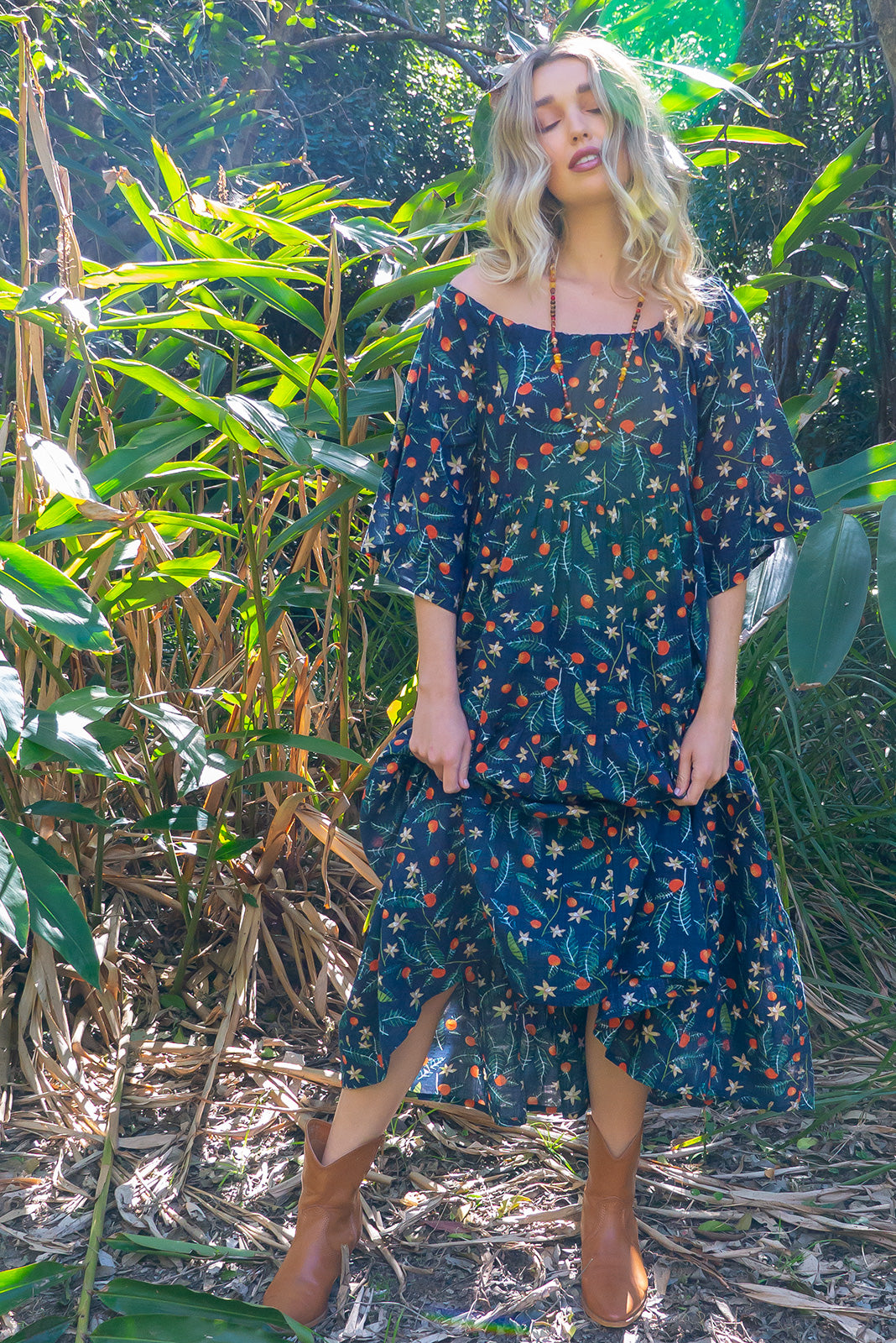 Lulu Liberty Orange Orchard Swing Maxi Dress is a bohemian dream made from a rayon and cotton blend fabric with a navy base scattered with daffodils and oranges, features 3/4 length sleeves and a waist tie belt.