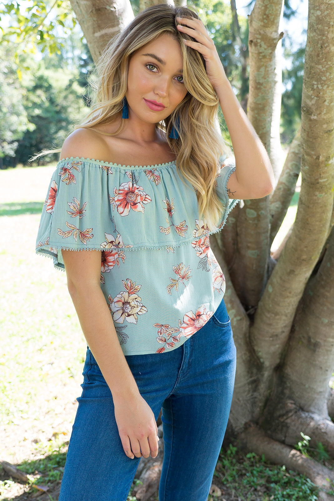 Macy Frill in Sage Green Off the shoulder top with an elastic neckline and drop over sleeve in a delicate sage green floral print a woven crinkle rayon