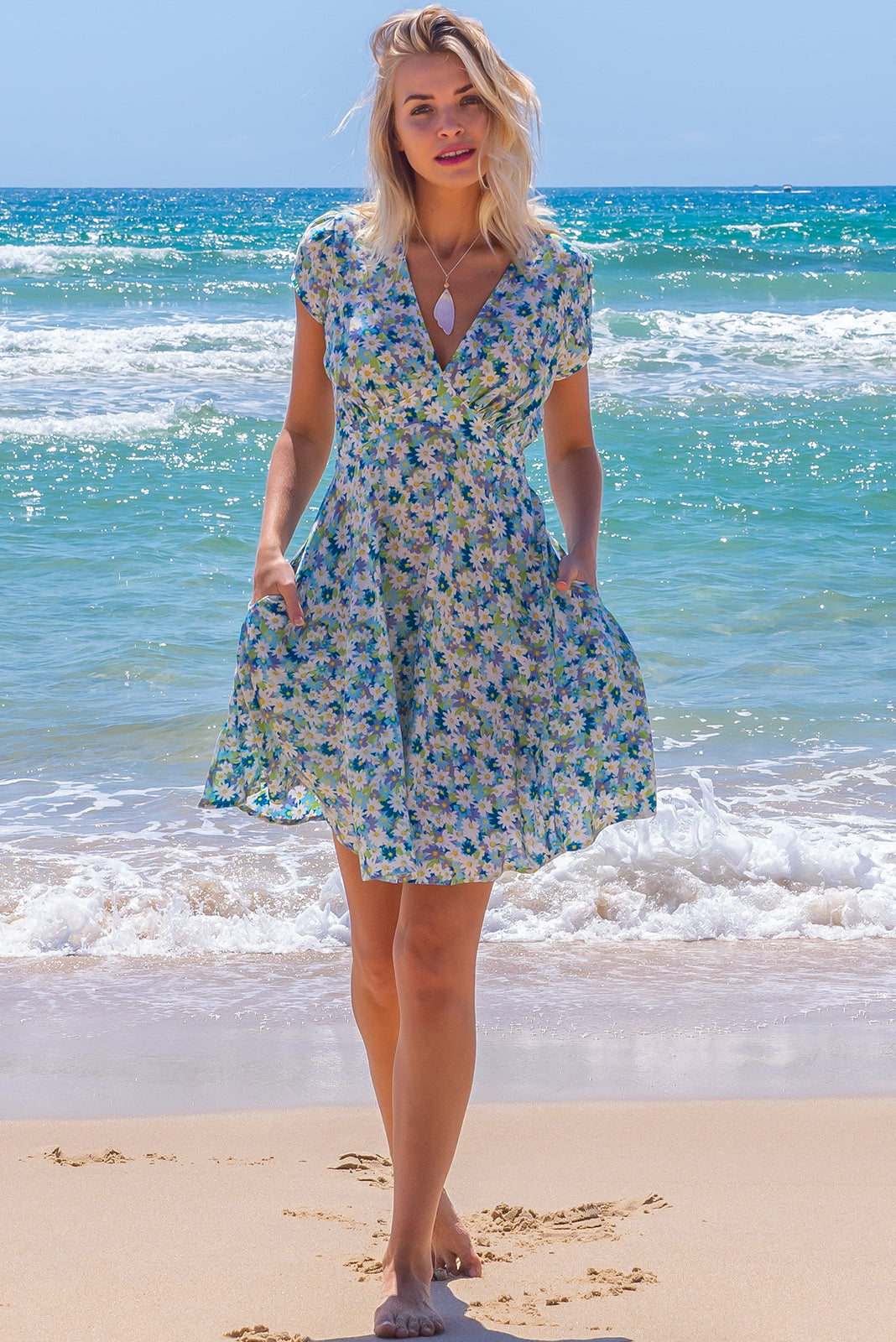 The Maggie May Celestial Blues Dress features waist features comfortable elastic shirring at back, cap sleeves, side pockets, flirty skirt draping from underneath bust and 100% in daisy print in blues and mints.