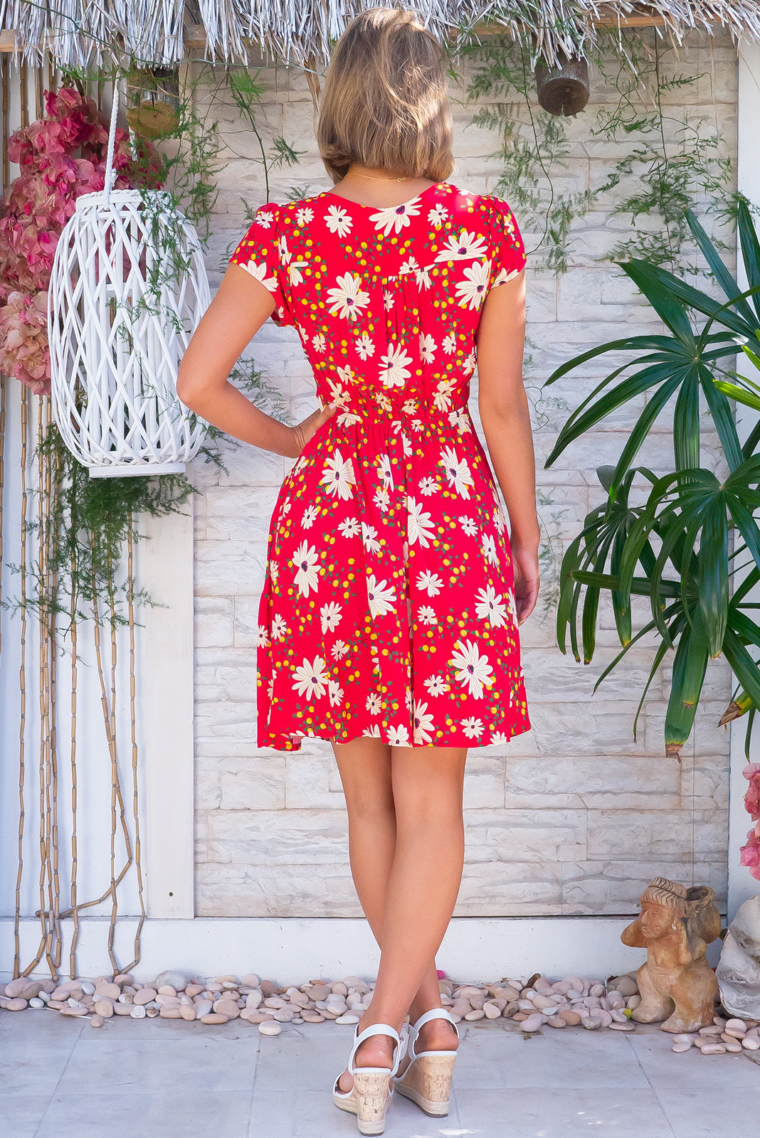 The Maggie May Days in Red Dress features gathered bust with basque underneath, waist features comfortable elastic shirring at back, cap sleeves, deep side pockets, flirty skirt draping from underneath bust and 100% rayon in red base with daisies and flower bud print.